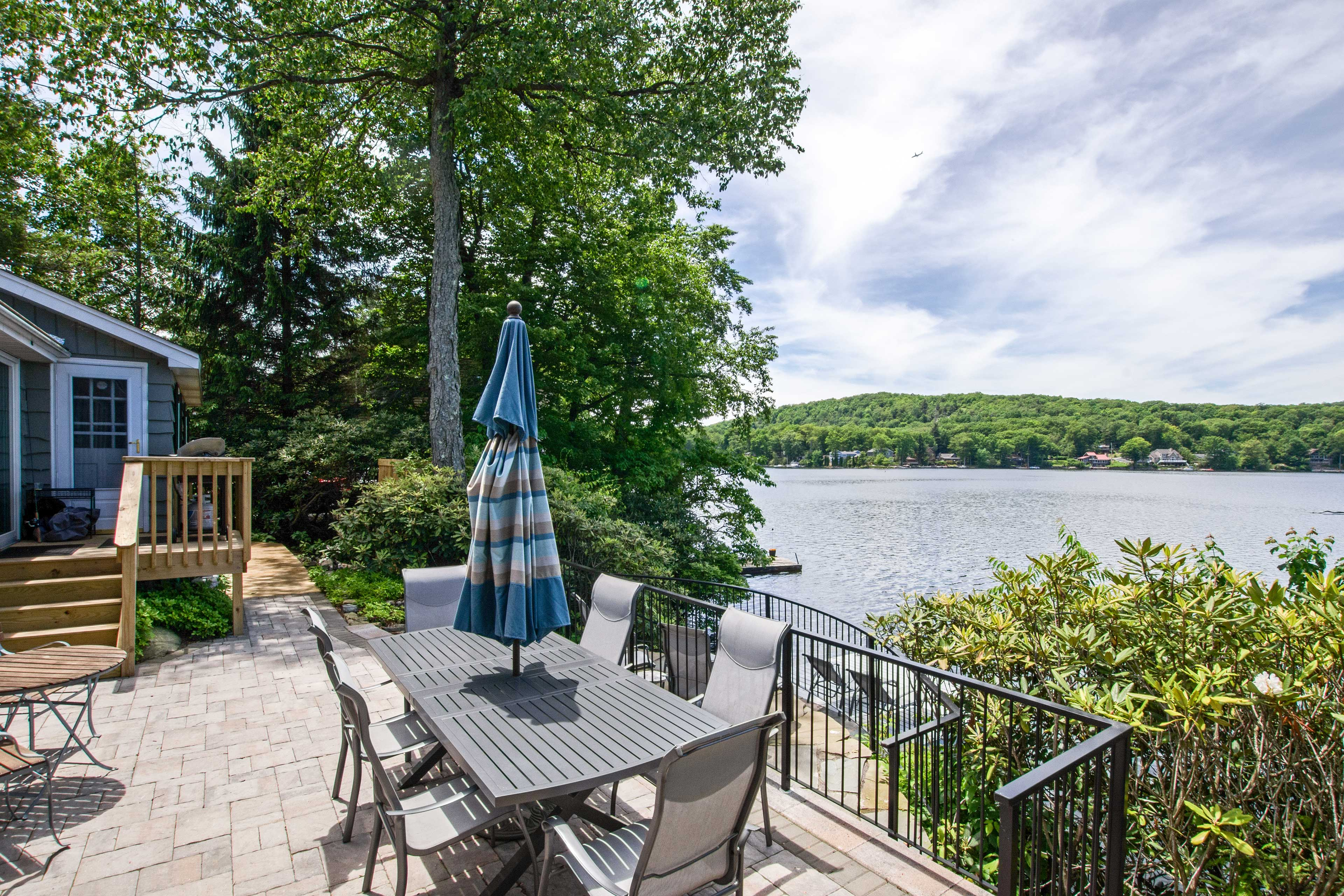 The waterfront property offers a private dock, water vessels & amenities for 10.