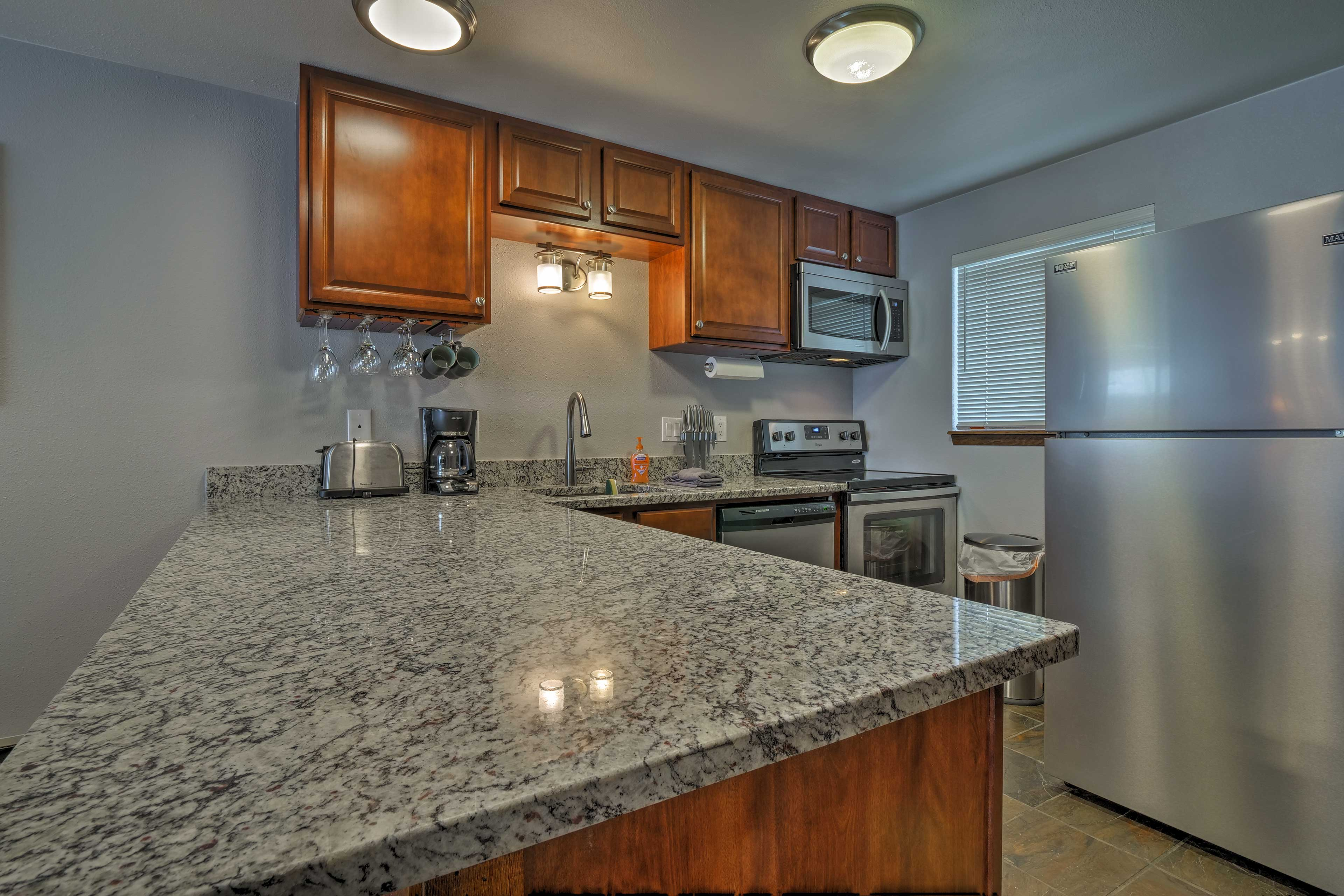 The fully equipped kitchen features granite counters and new cabinets.