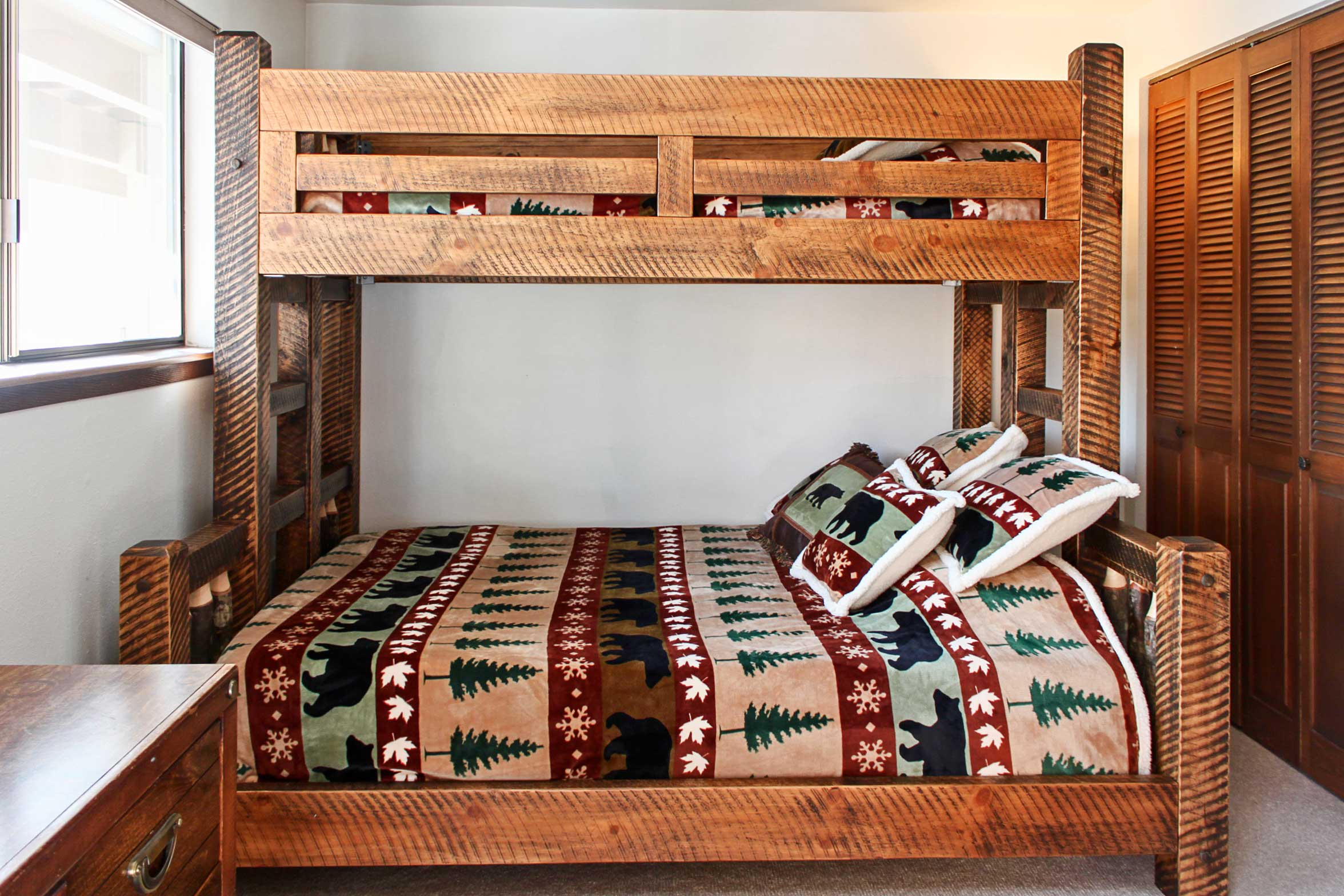 Climb under the covers of the extra long twin-over-queen bunk bed.