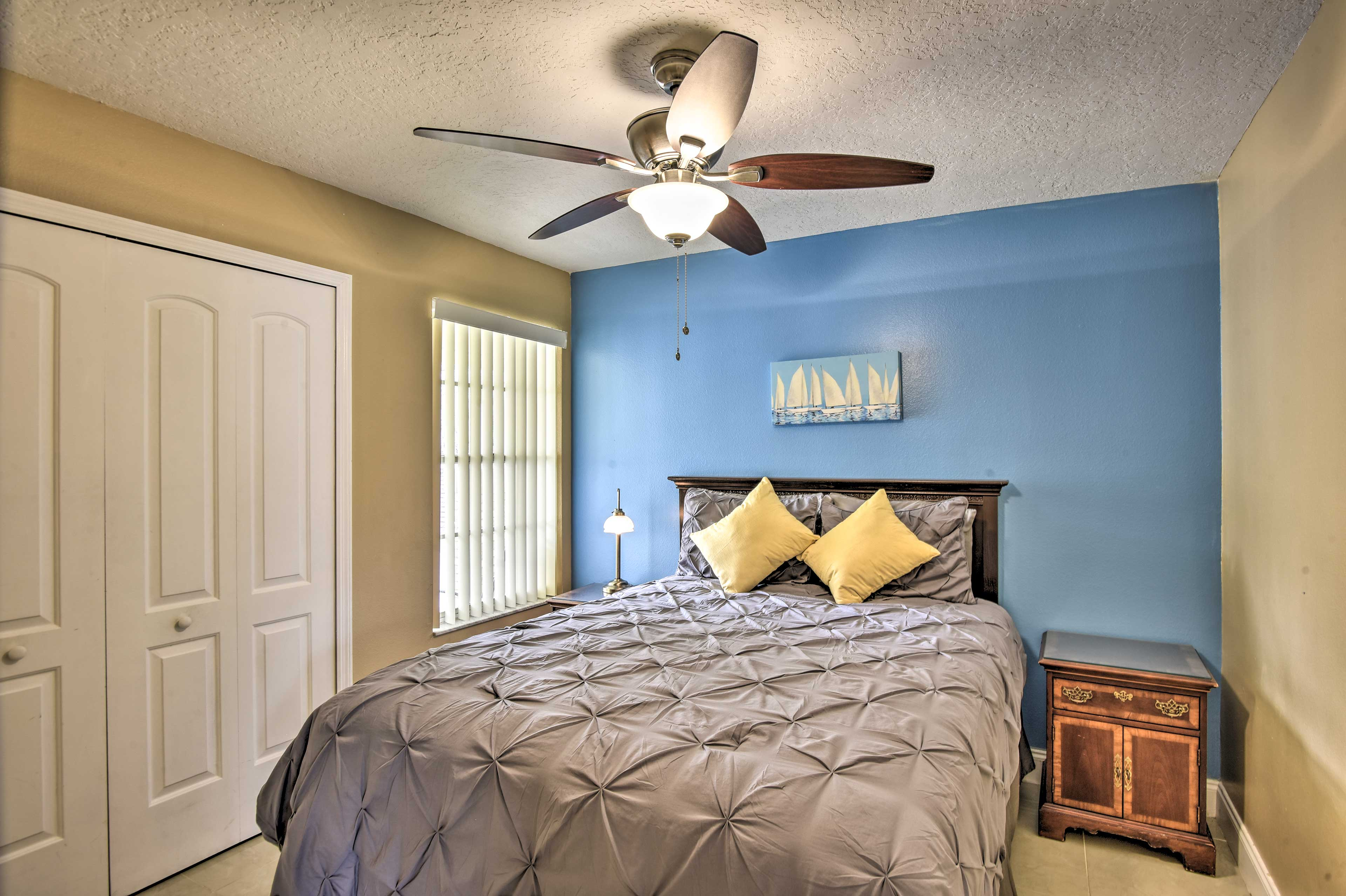 The second bedroom features a comfortably made queen bed.