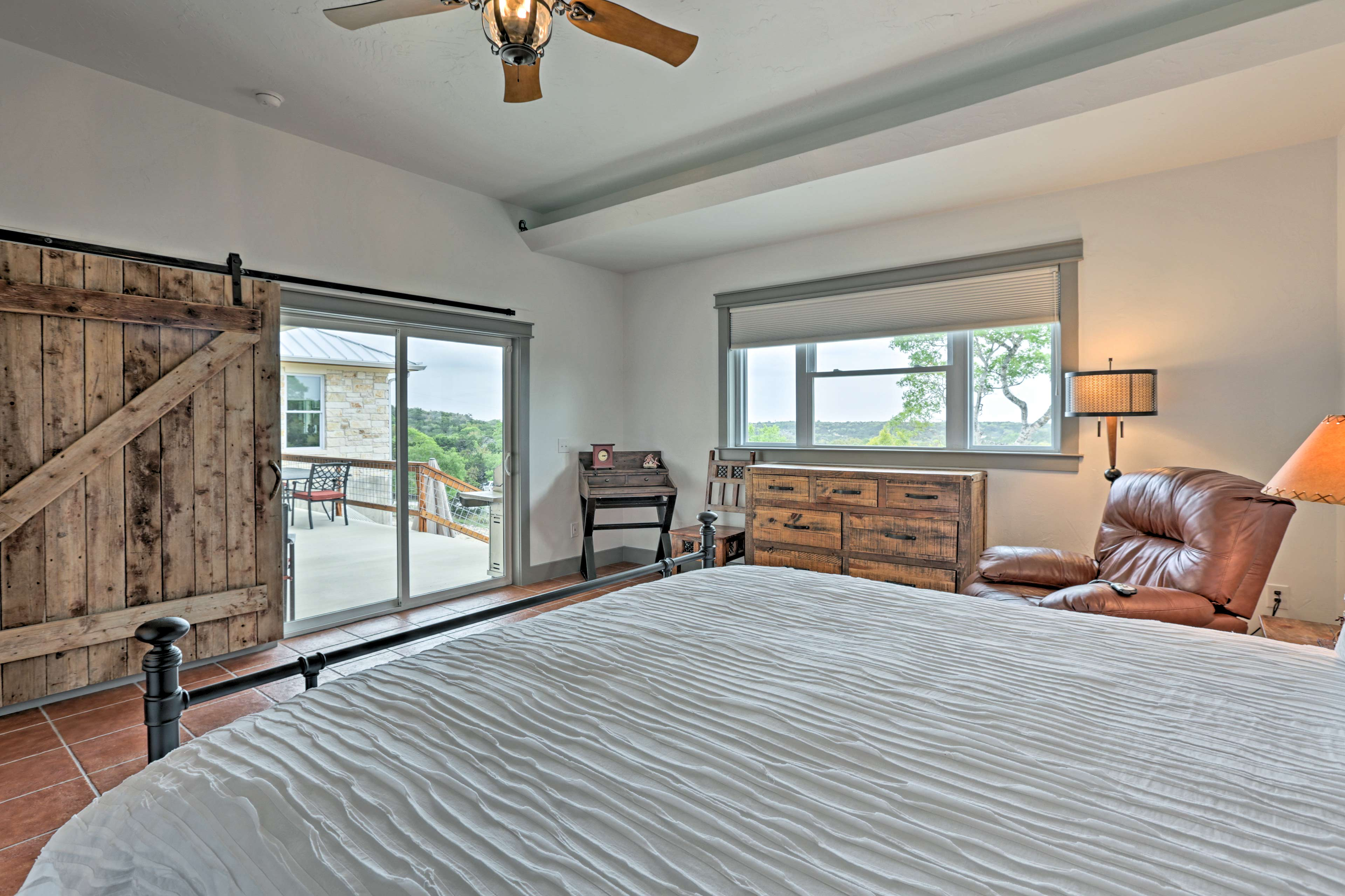 Glass sliding doors connect the master bedroom to the main deck.