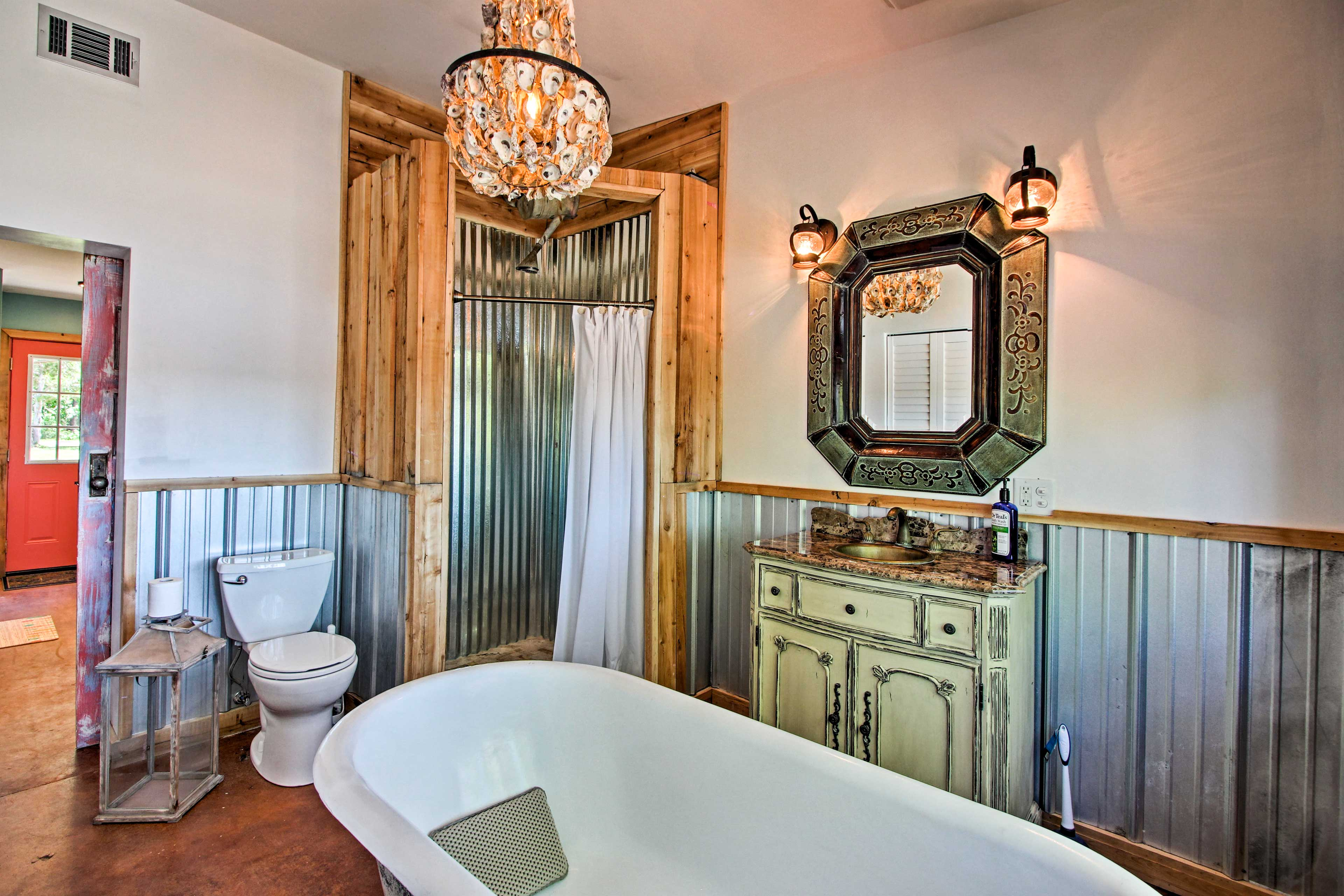 The rustic, pink barn door slides aside to expose this spa-like bathroom.