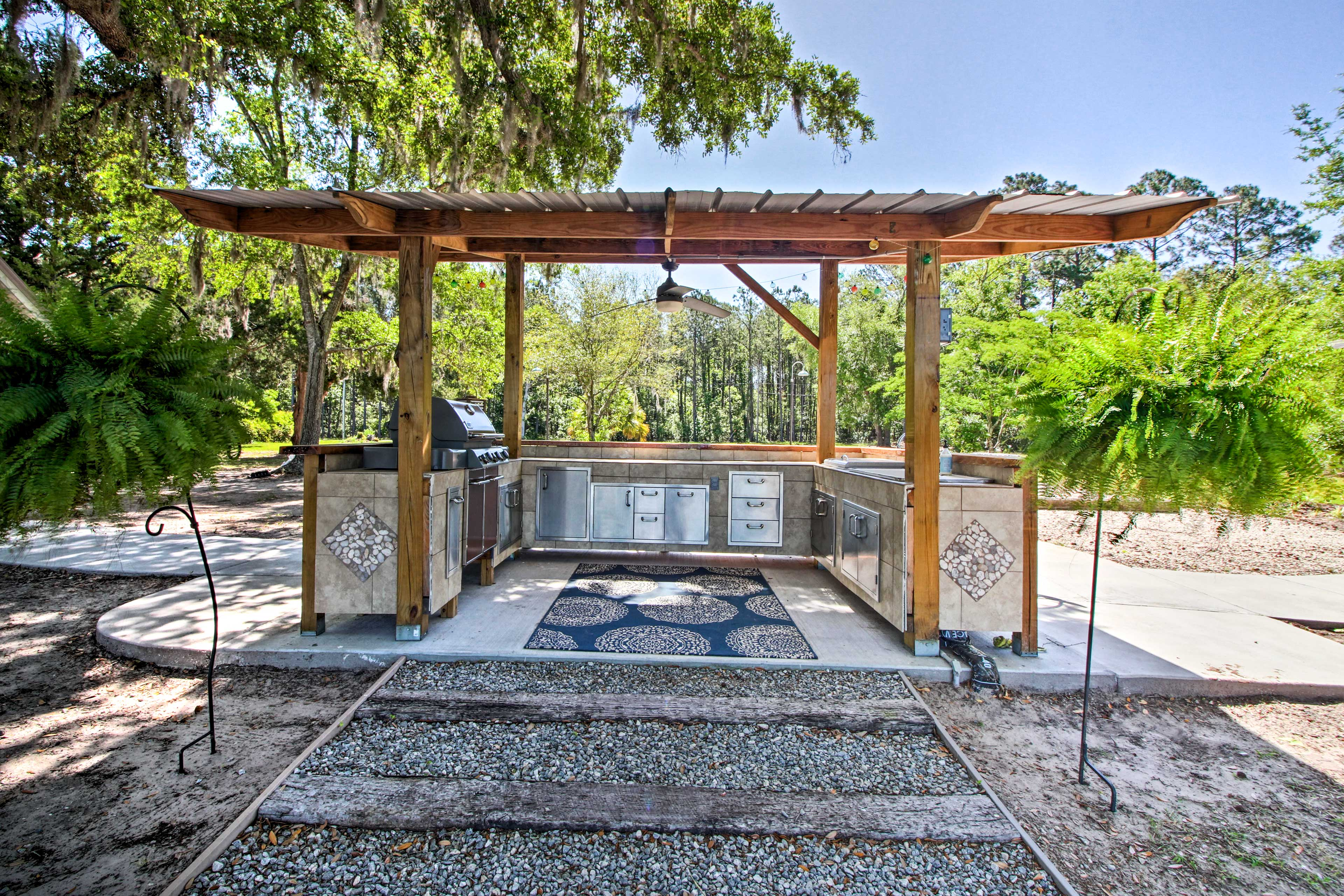 Enjoy the impressive shared outdoor kitchen equipped with a gas grill and fan.