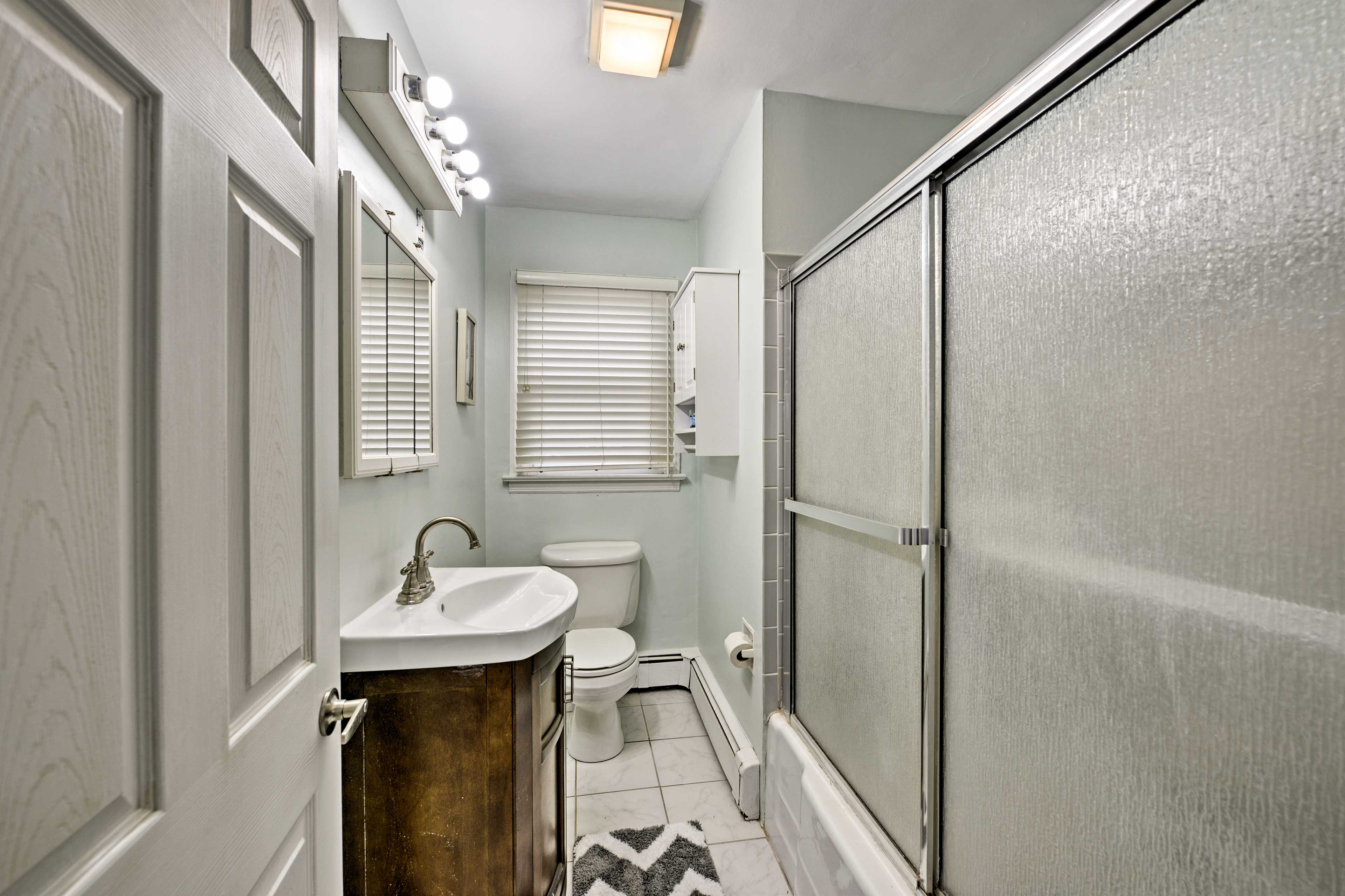 The full bathroom includes a shower/tub combo.