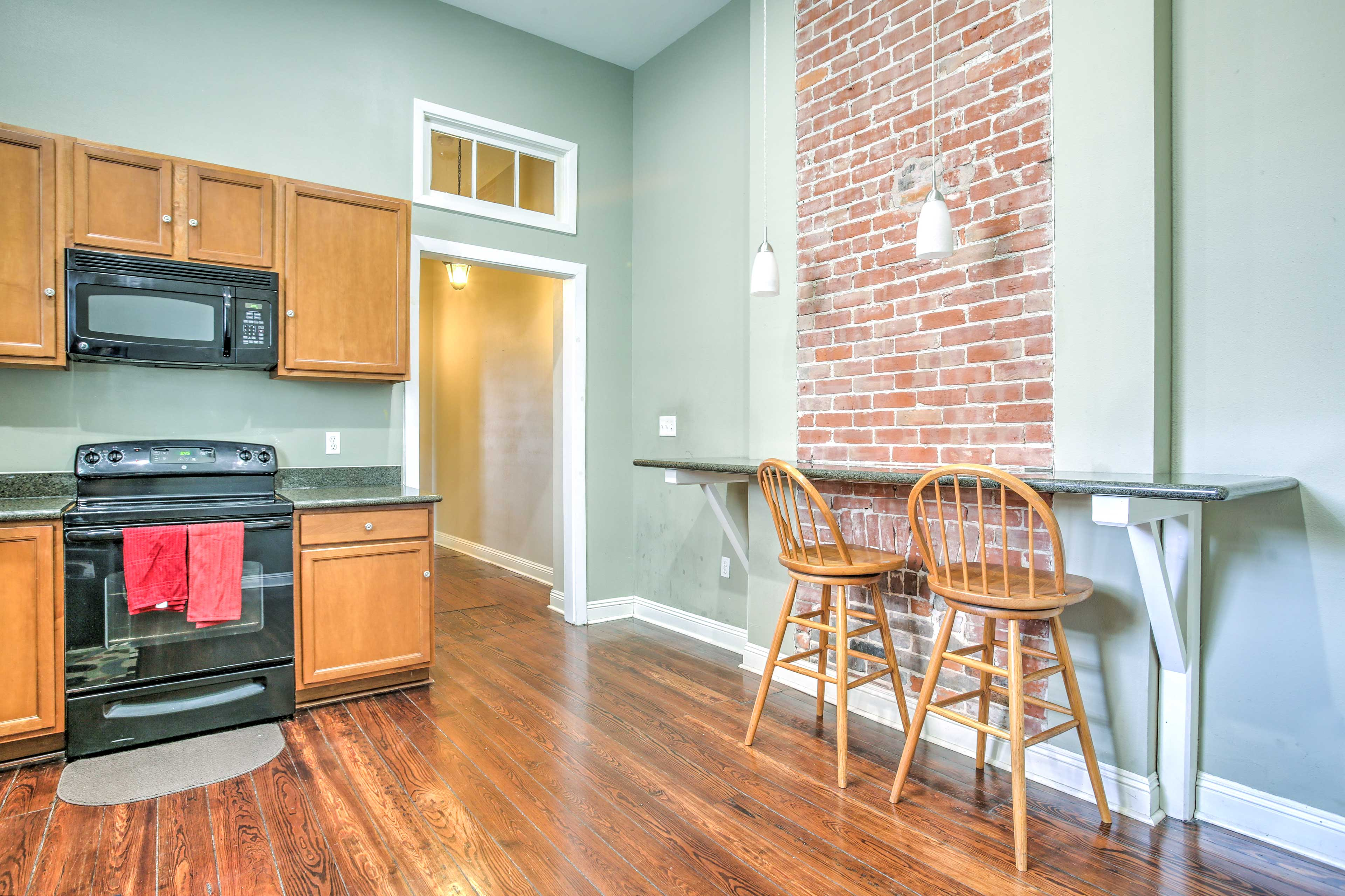 A built-in counter and exposed brick wall detail the fully equipped kitchen.