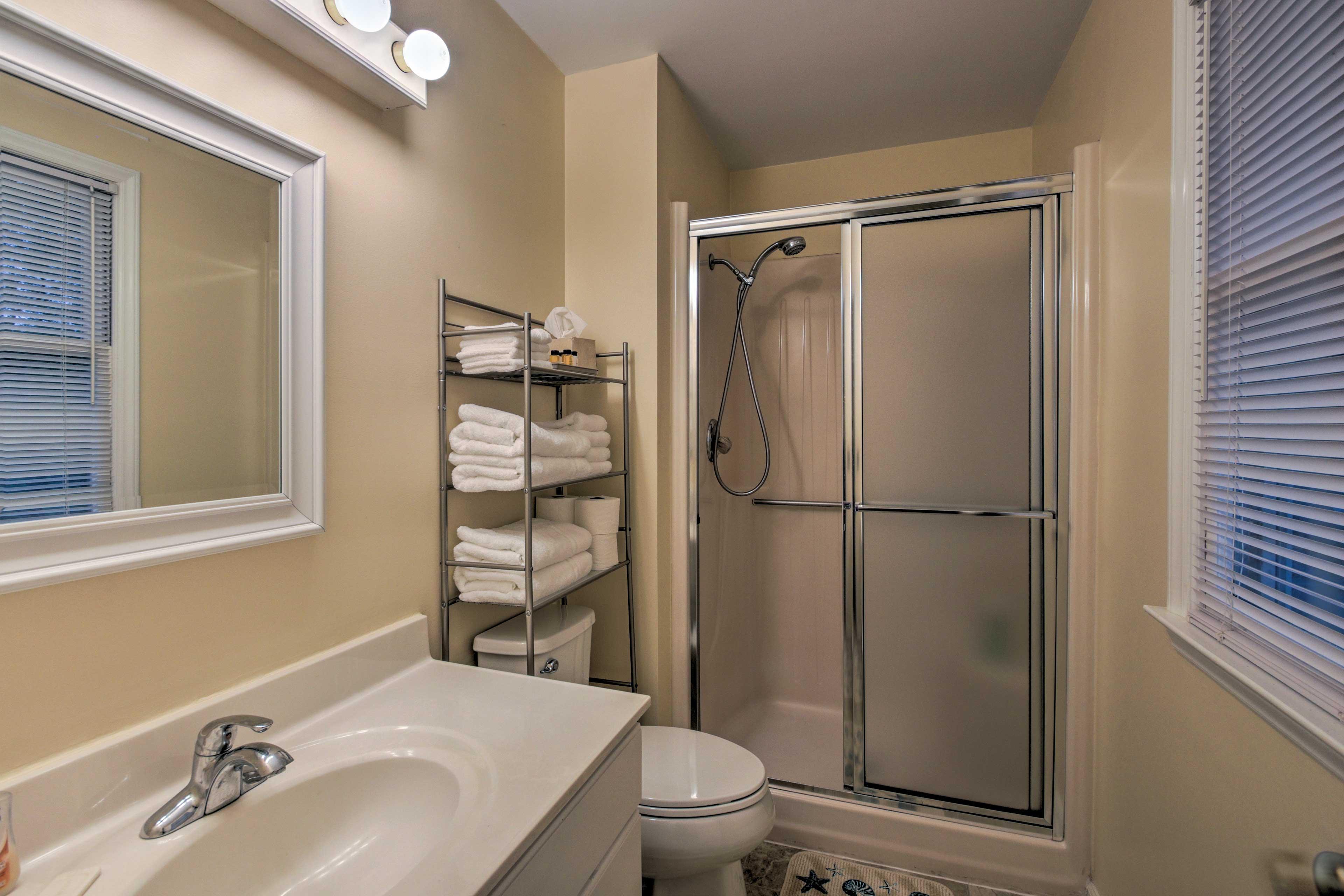 Sliding glass doors frame the walk-in shower in this bathroom.