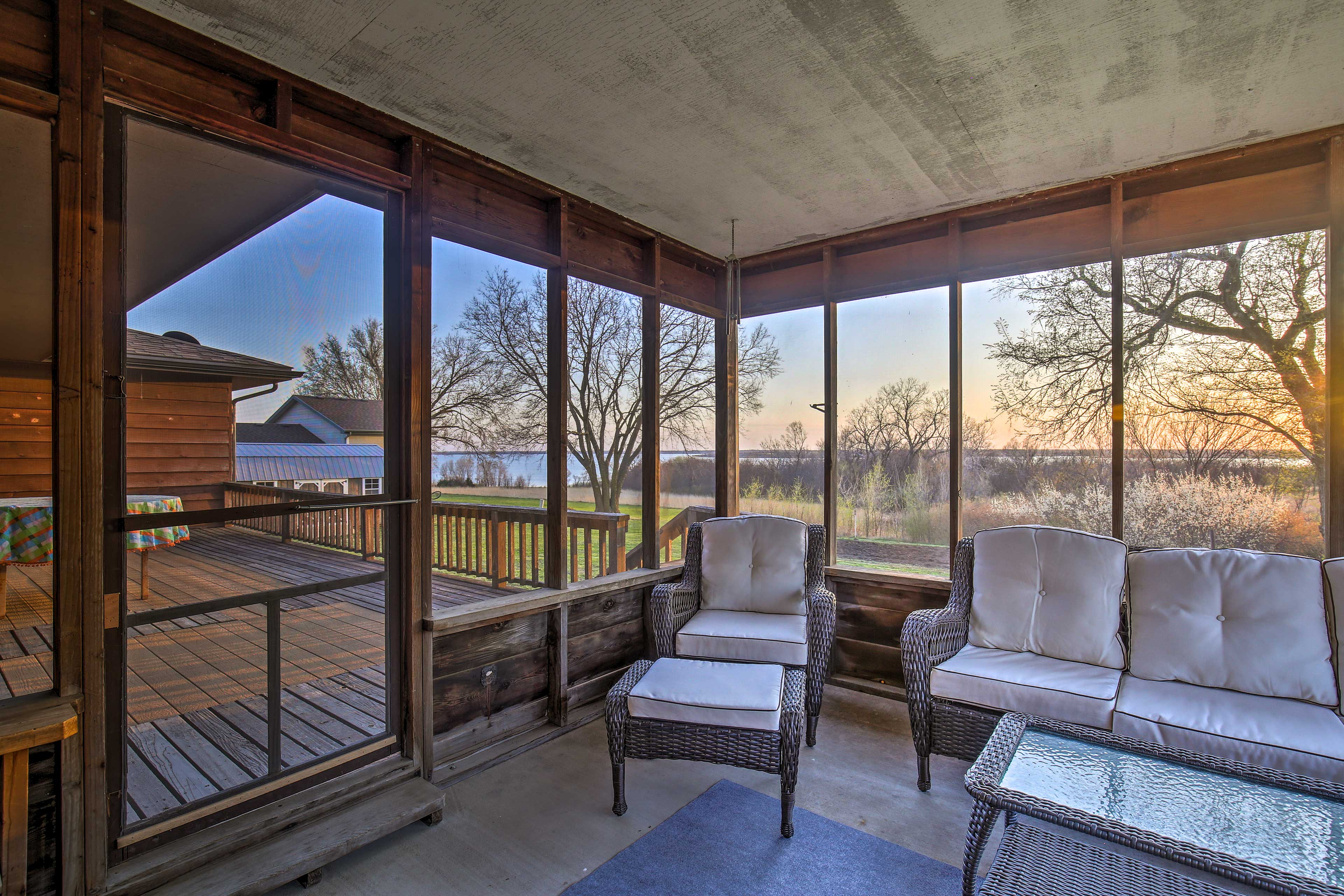 The porch overlooks the grassy backyard and the lake.