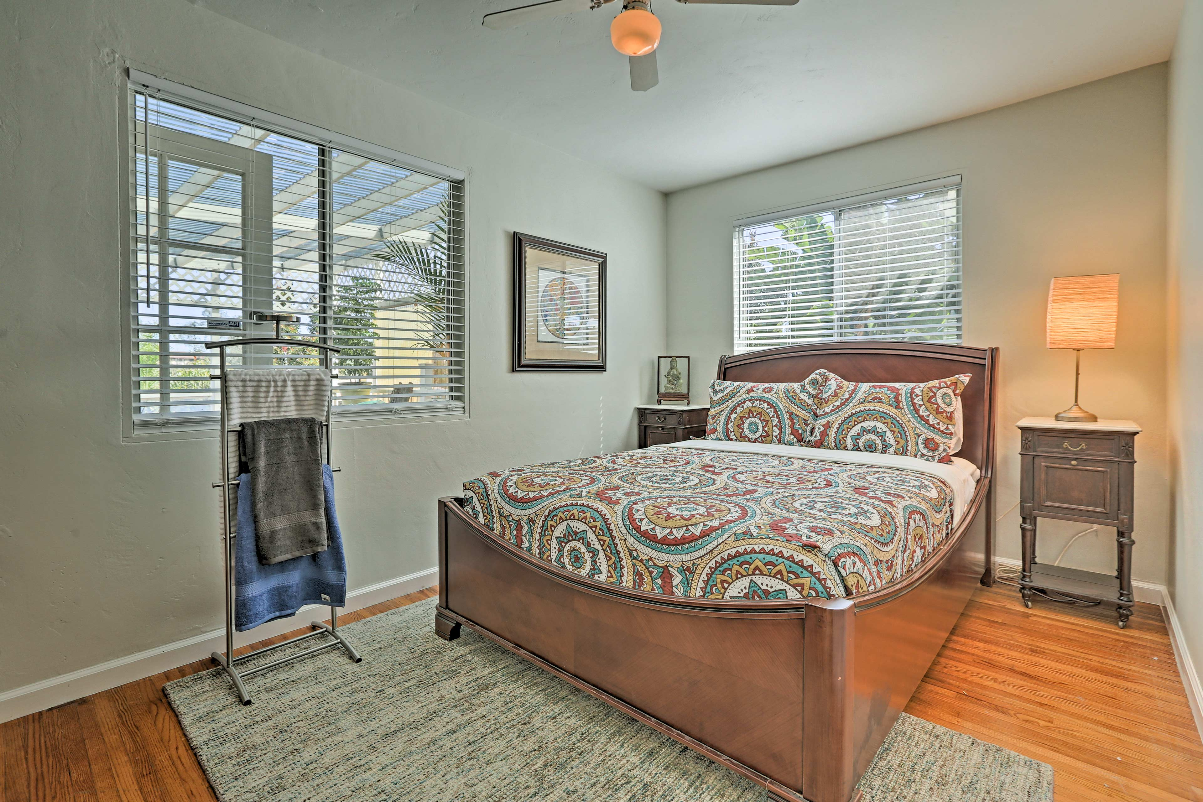The second bedroom offers a calming atmosphere with a queen bed and ceiling fan.