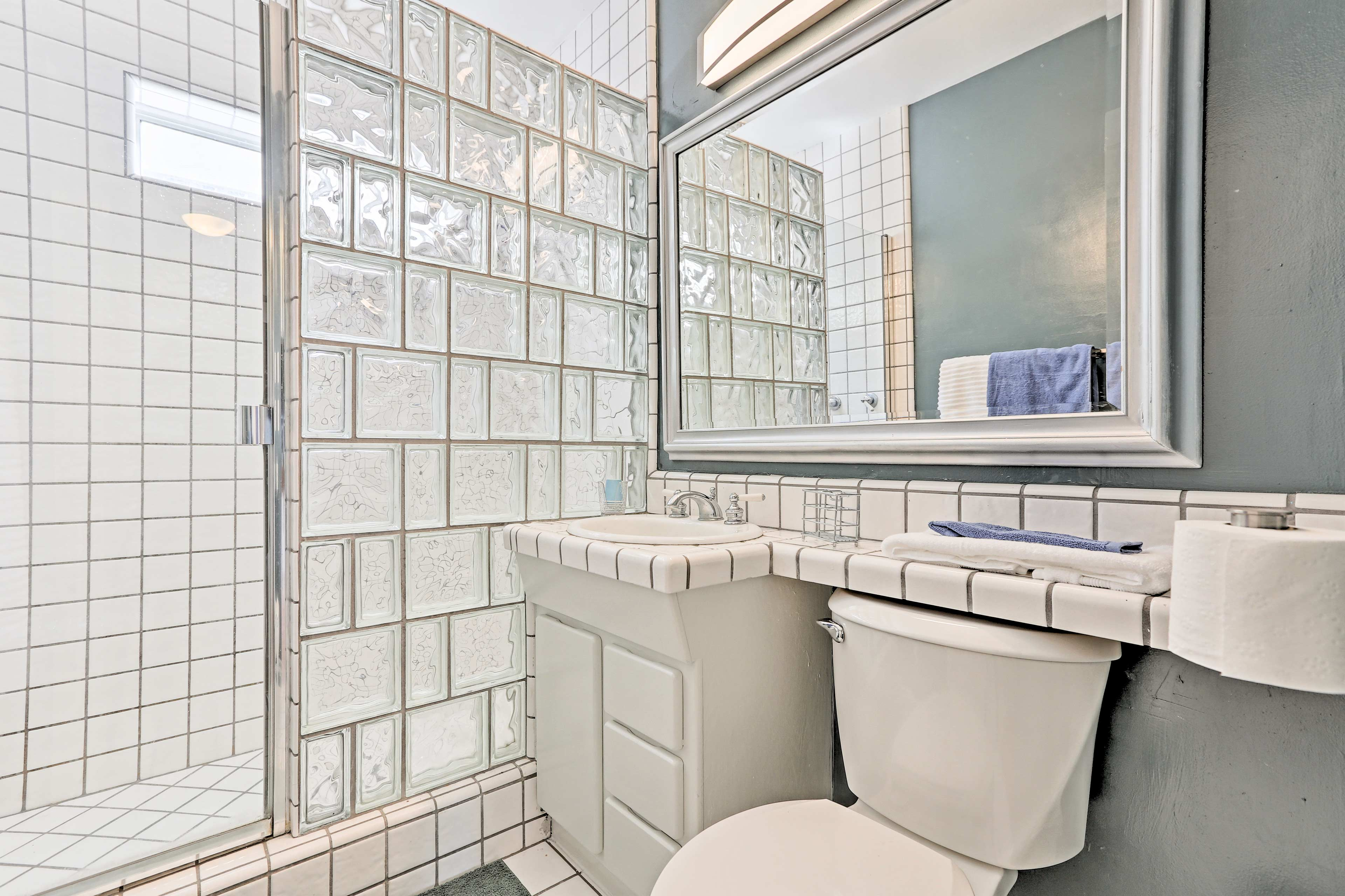 This pristine bathroom comes stocked with fresh, soft towels for guests' comfort.