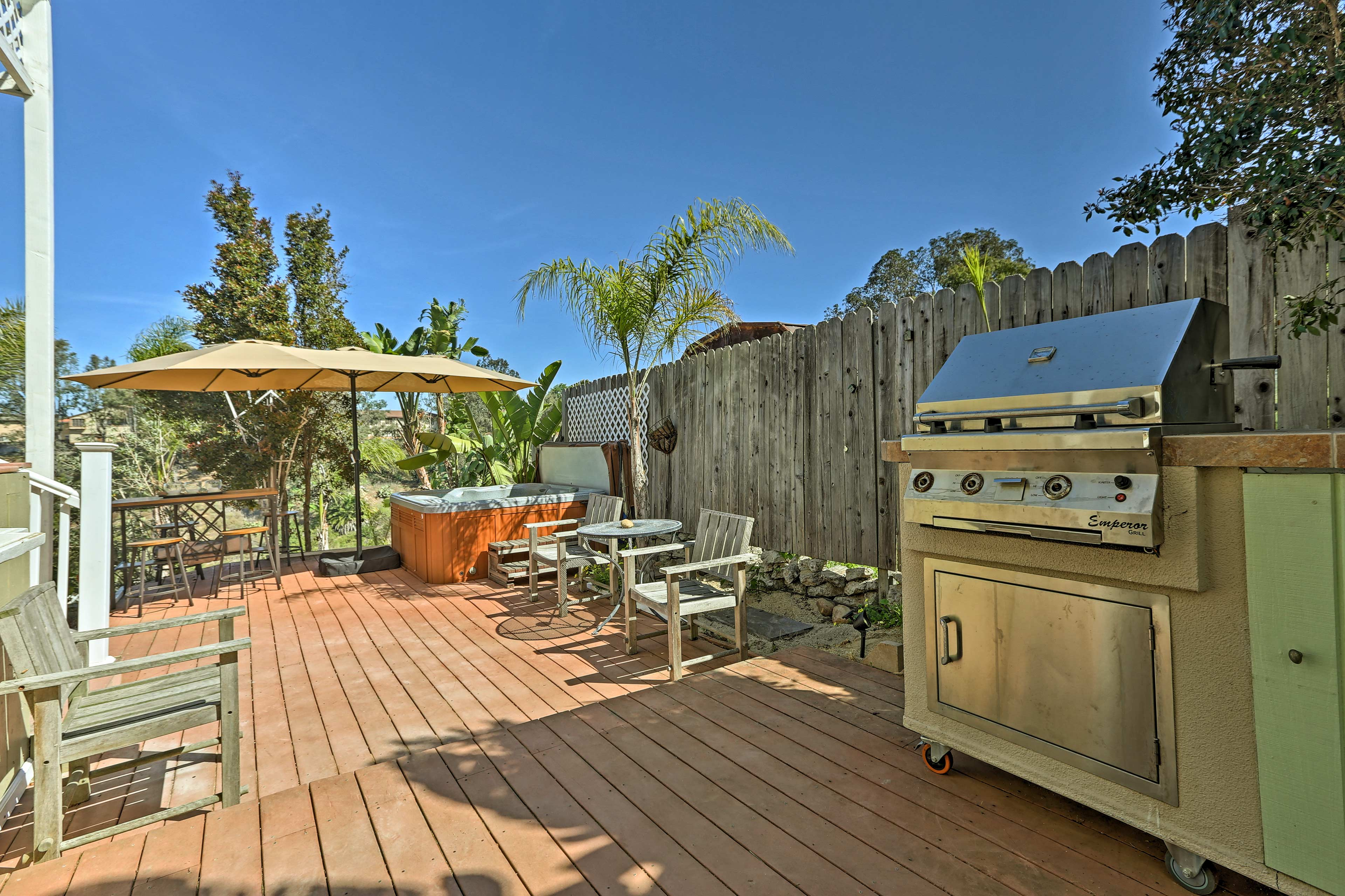 This true entertainment patio features a hot tub, gas grill, and bar area.