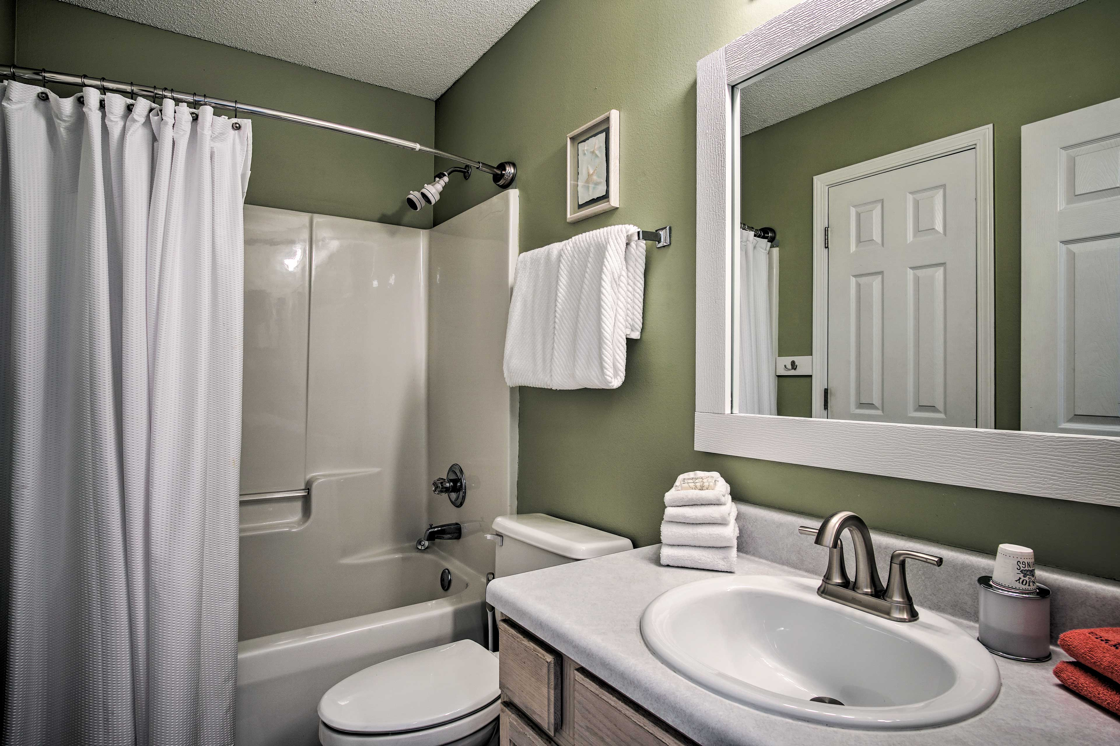 A traditional shower/tub combo is provided in this full bathroom.