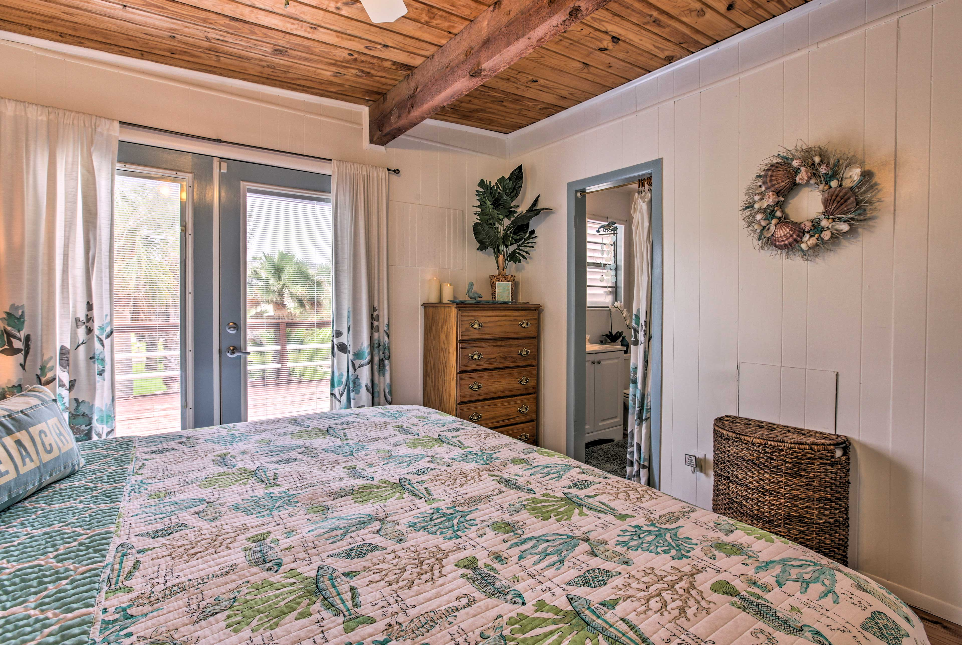 Wake to natural light and tropical views filtering through the glass door.