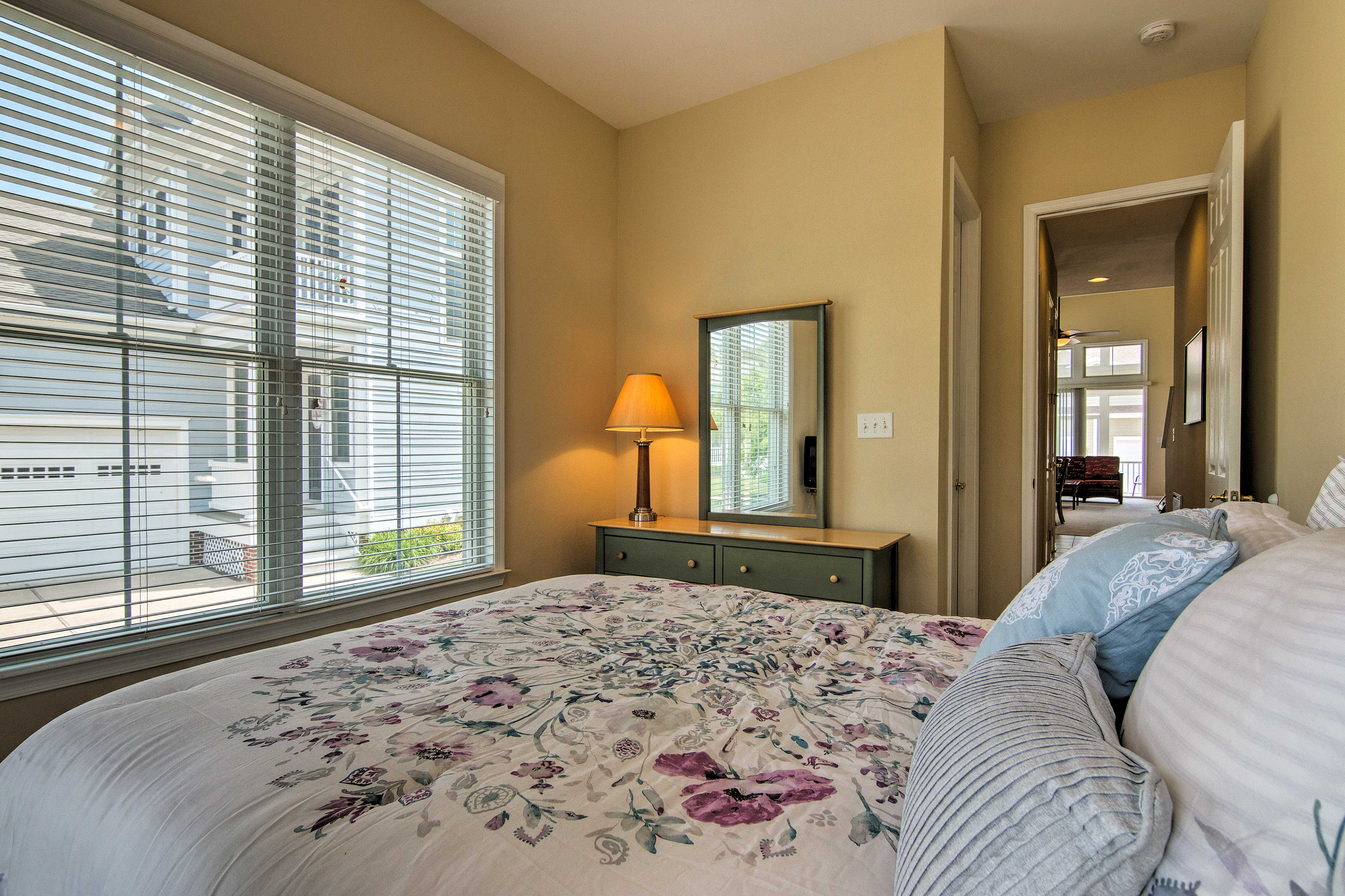 A third bedroom has a cloud-like queen bed and picture windows.
