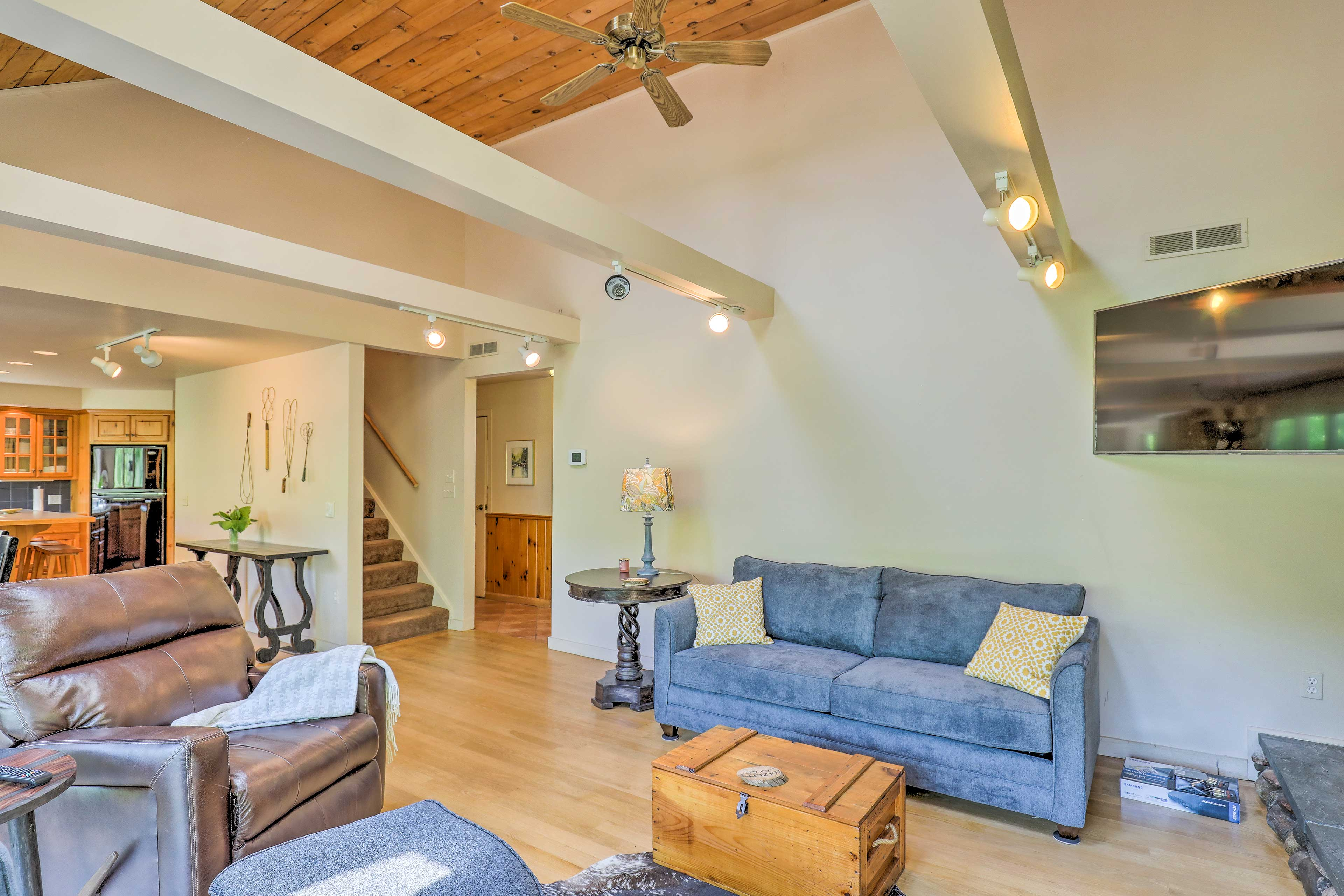 The open living space hosts comfortable seating and a flat-screen satellite TV.