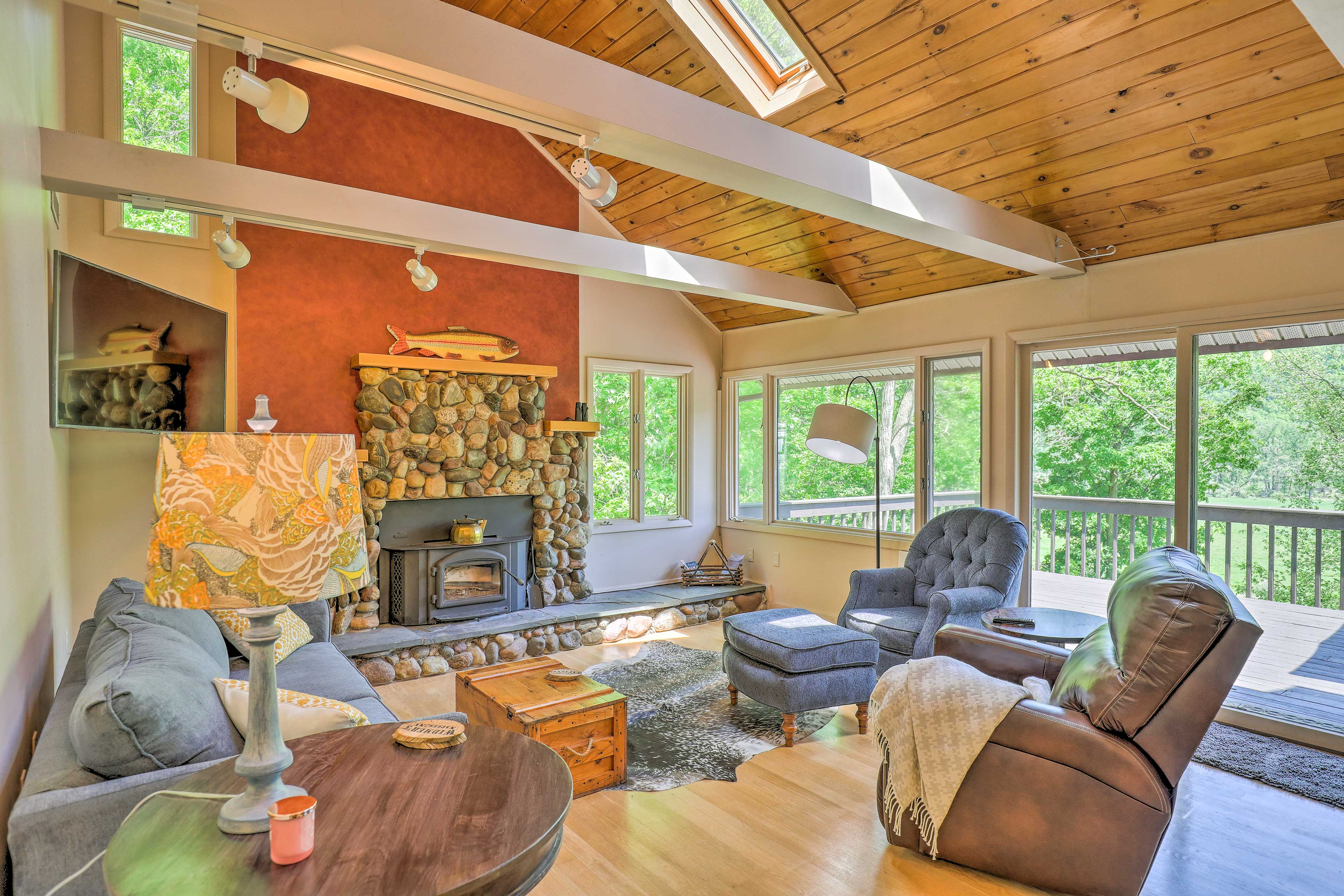 Wall-to-wall windows and sliding glass doors open to the deck and valley.