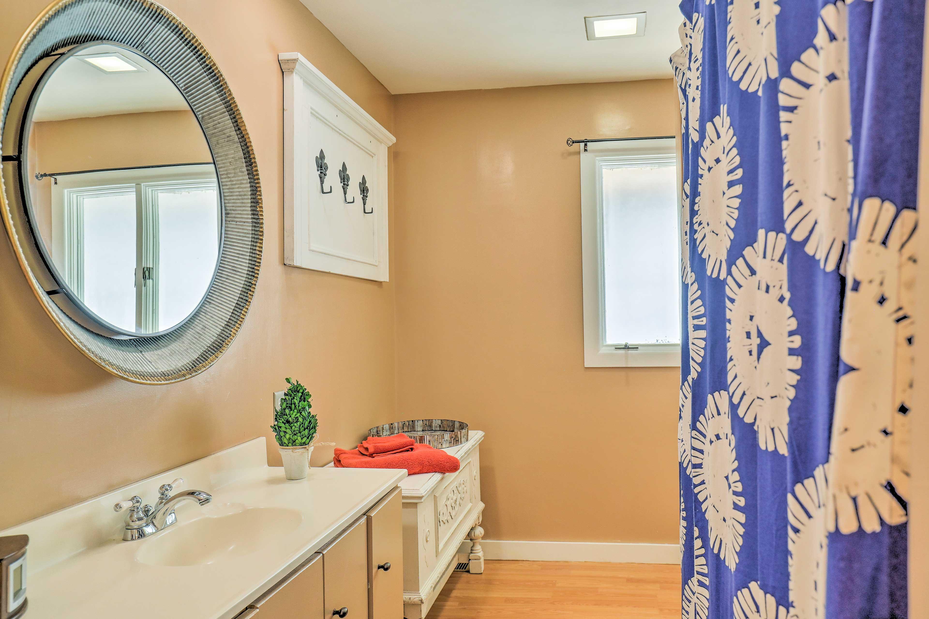 A circular mirror and quirky decor furnish this full bathroom.