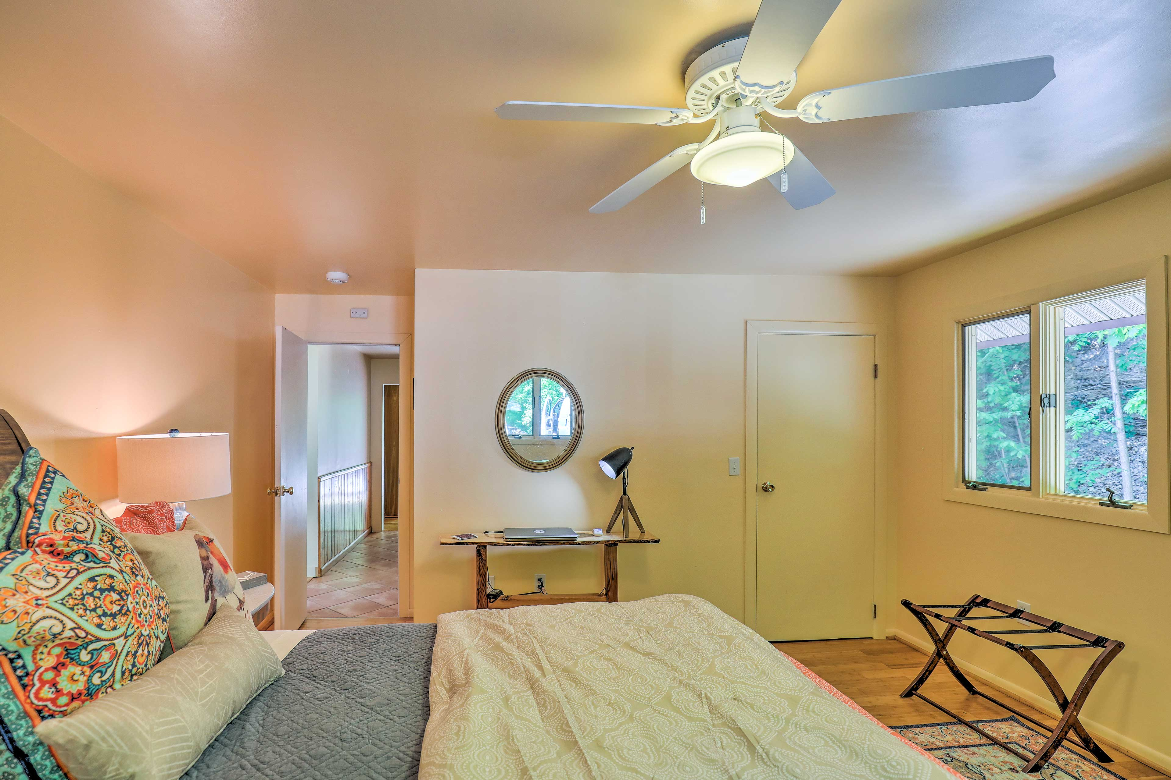 Two windows let plenty of natural light stream in to brighten the cozy bedroom.