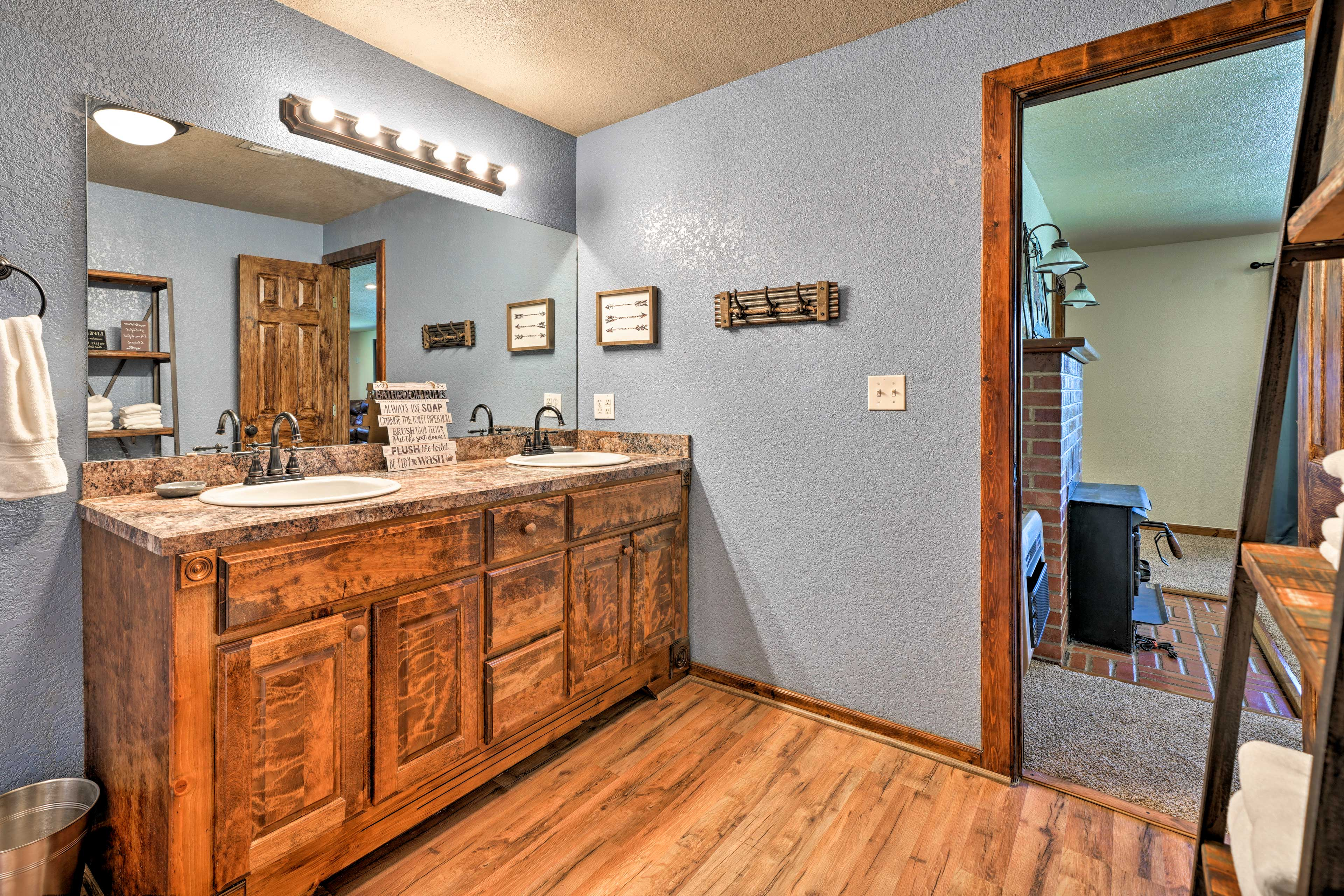 The full bathroom boasts double sinks and bright lighting.