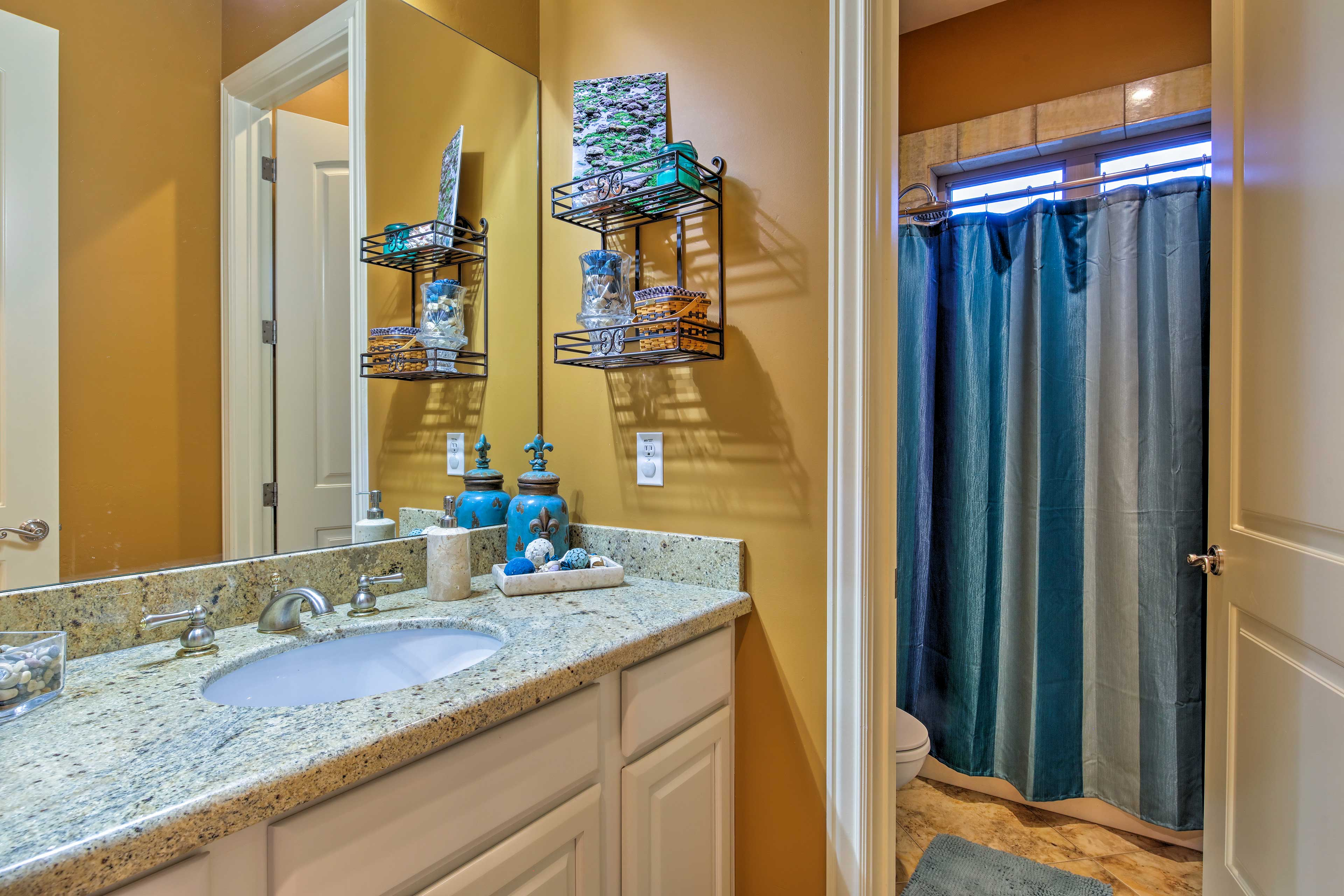 The large counter furnishing this full bathroom provides plenty of storage space
