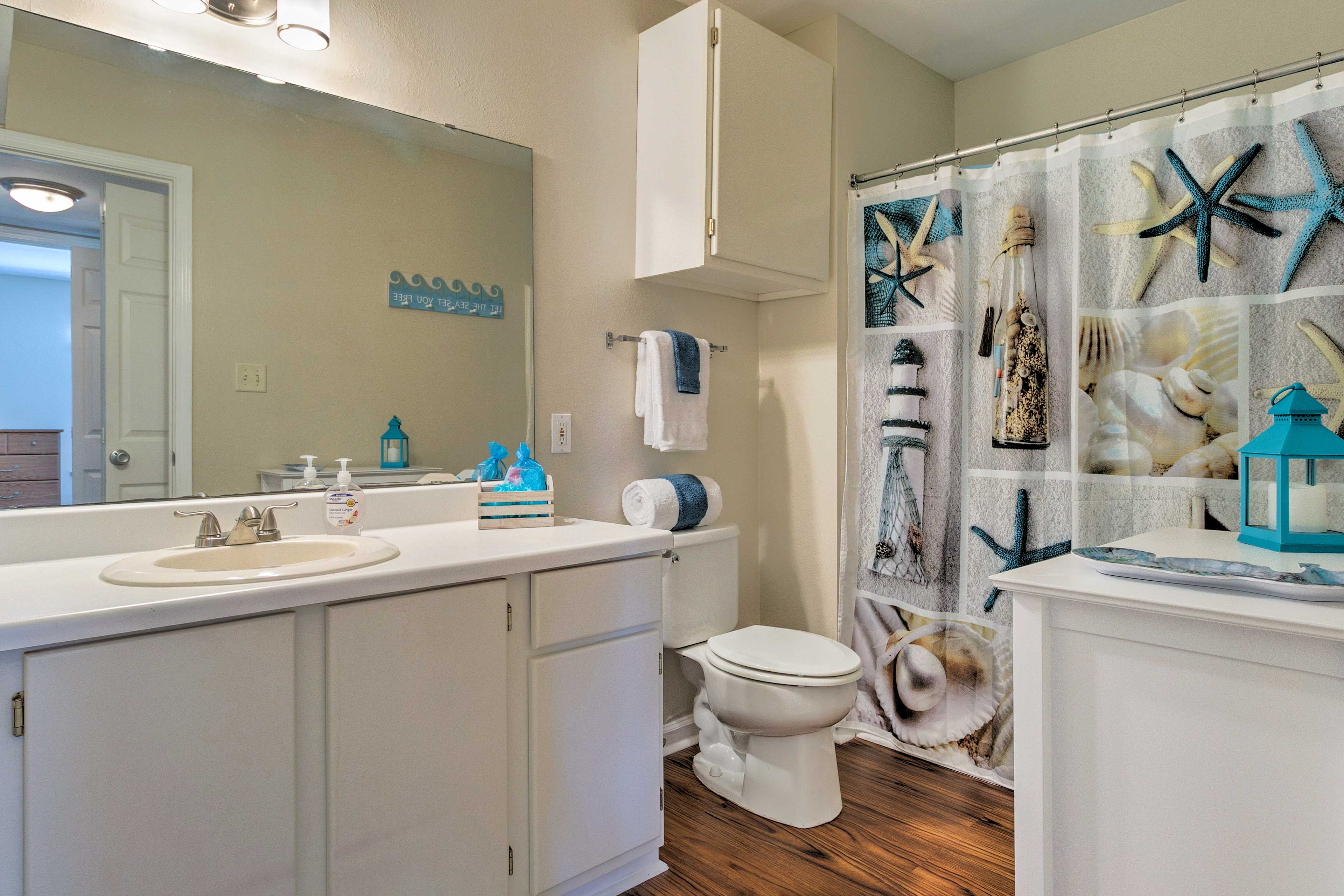 The first bathroom has a single sink, vanity mirror, and a shower/tub combo.