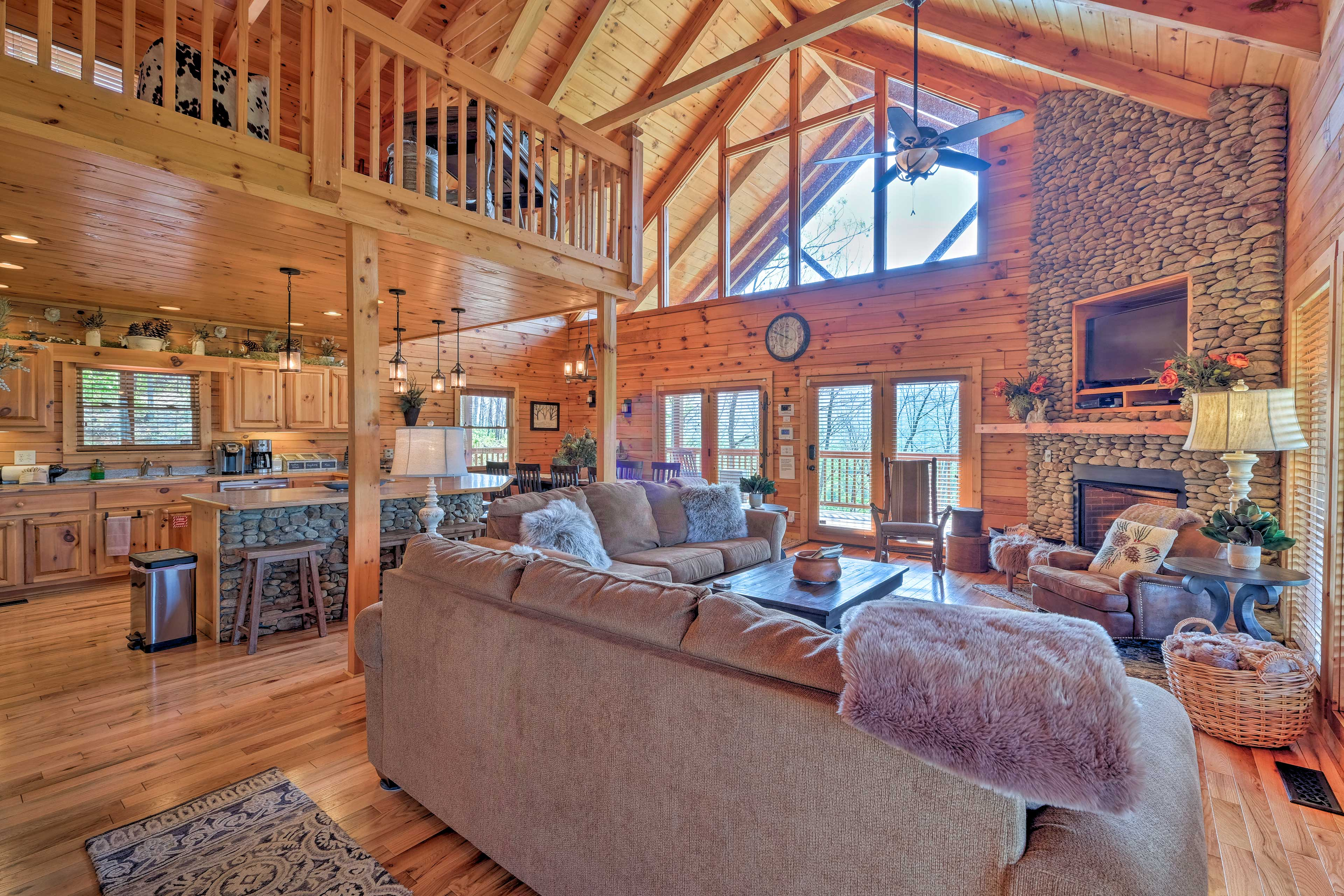 The great room offers stunning vaulted ceilings and a beautiful stone fireplace.