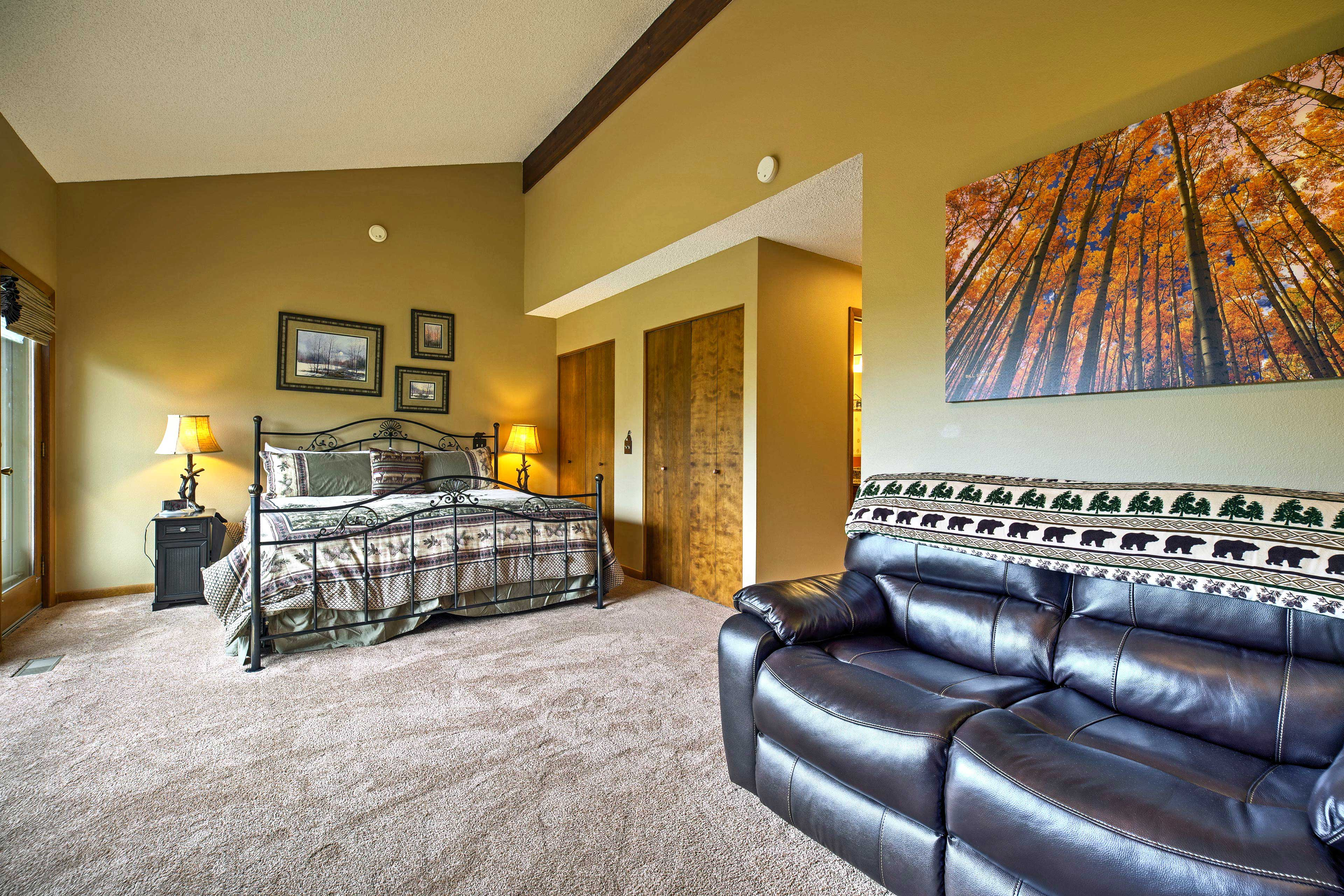 The master bedroom has a comfortable love seat in front of the fireplace.