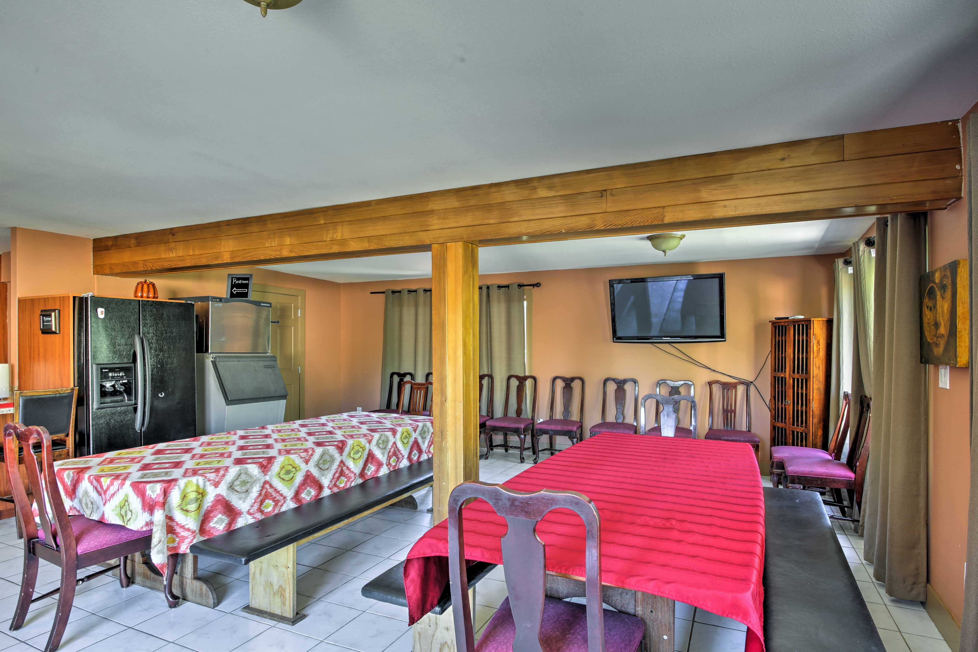 The mess hall has elongated wood dining tables & a flat-screen Smart TV.