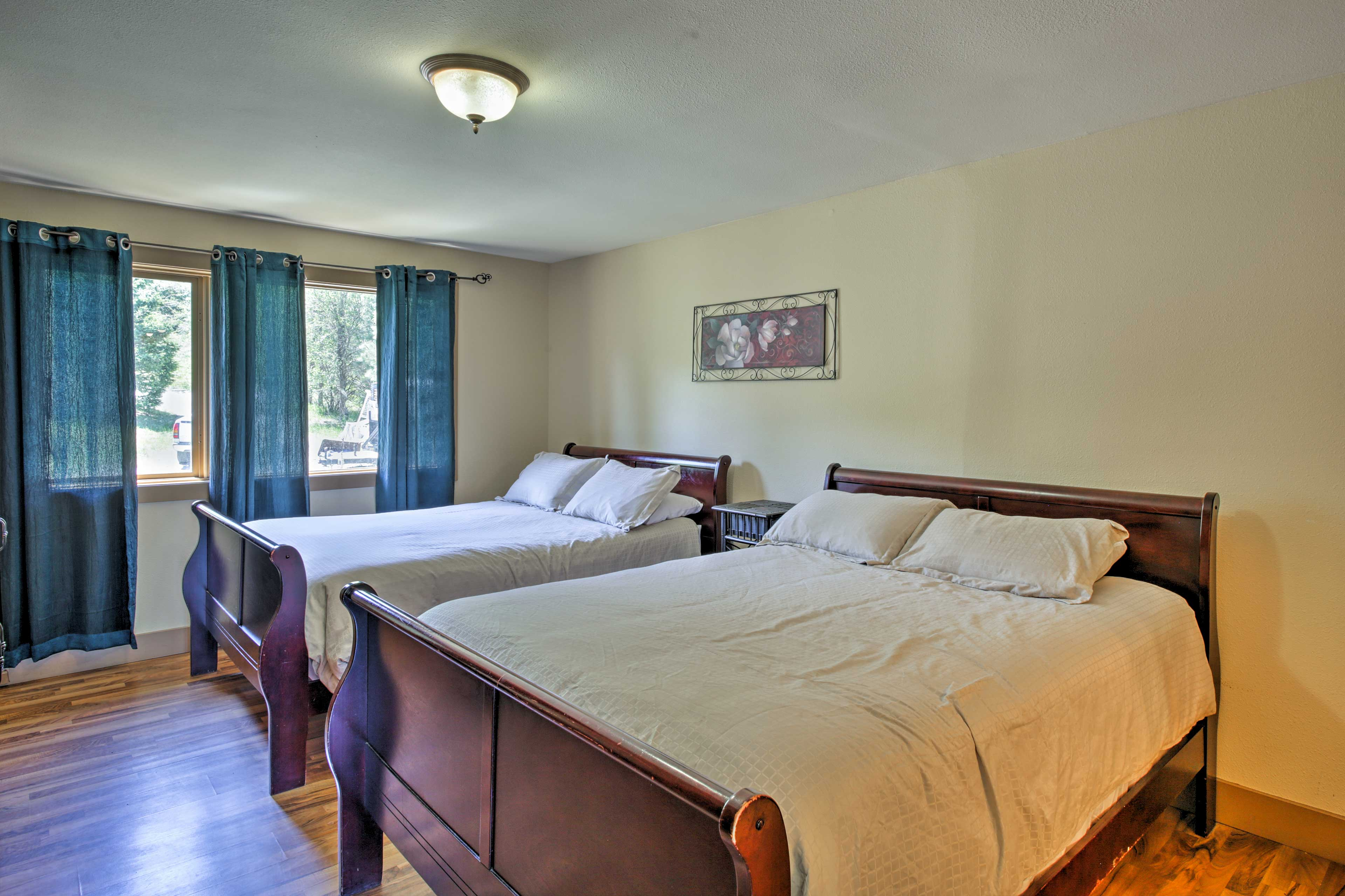 This bedroom has 2 queen beds and window views of the forested slopes.