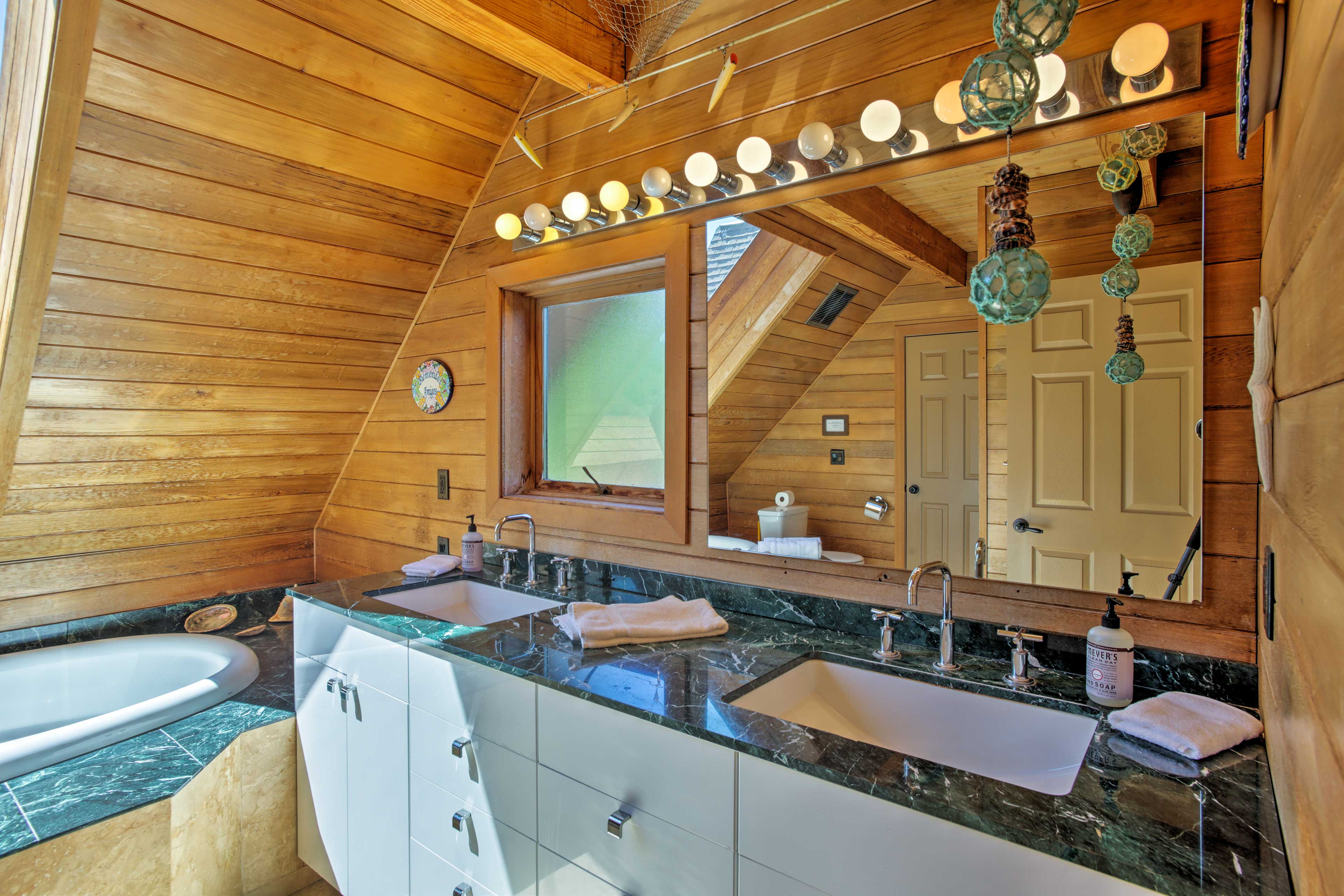 A luxurious bathroom has double sinks & ample storage space.