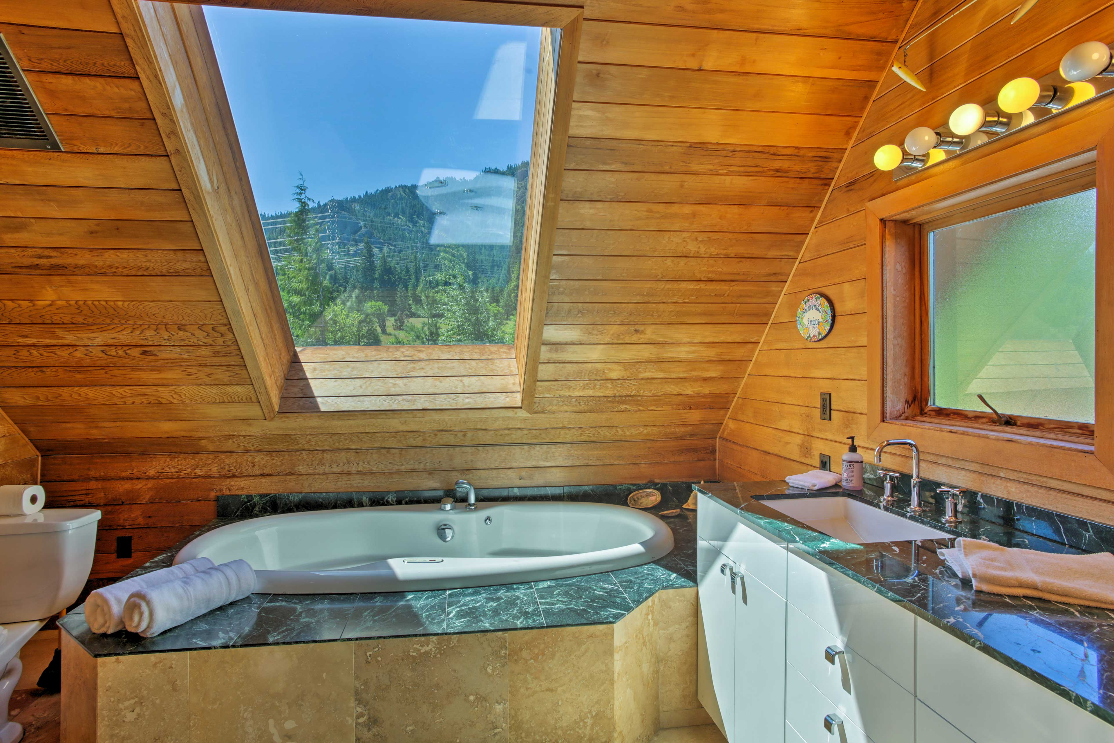 The bathroom has a sunken tub with a skylight letting in sunshine and views.