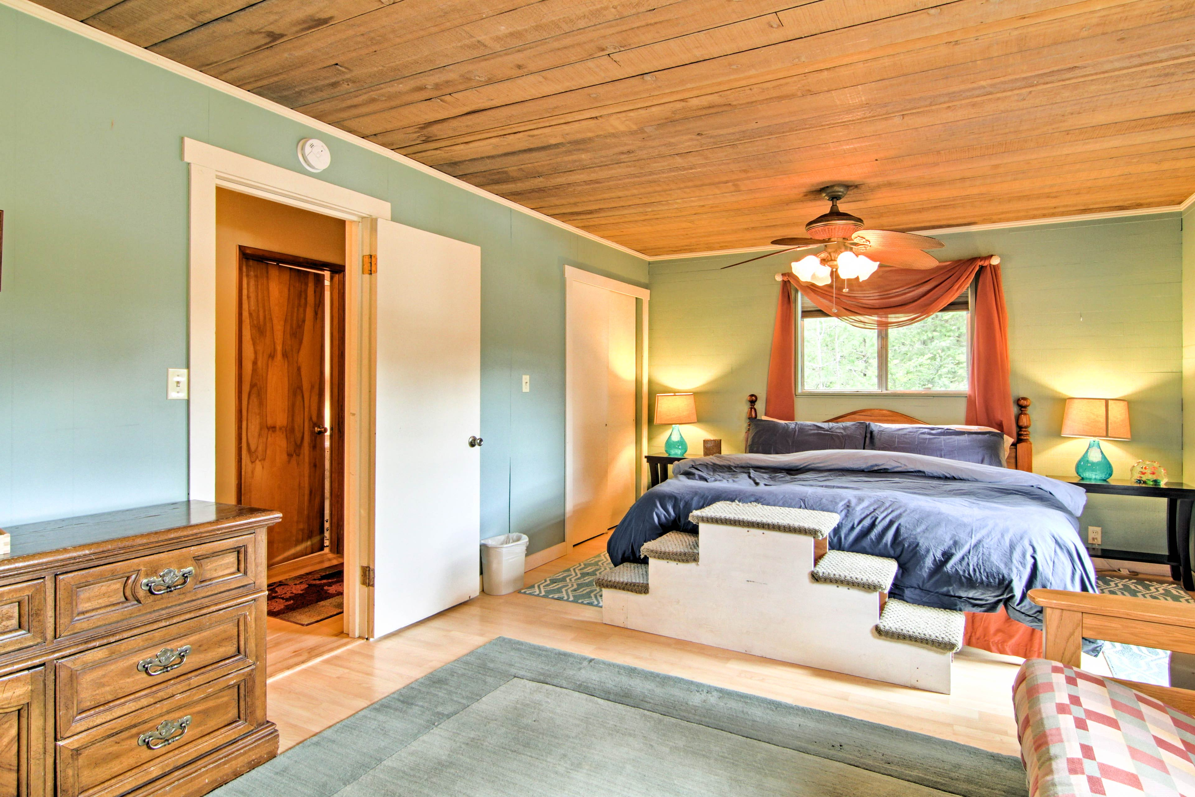 The bright master bedroom has rustic high wood-paneled ceilings.