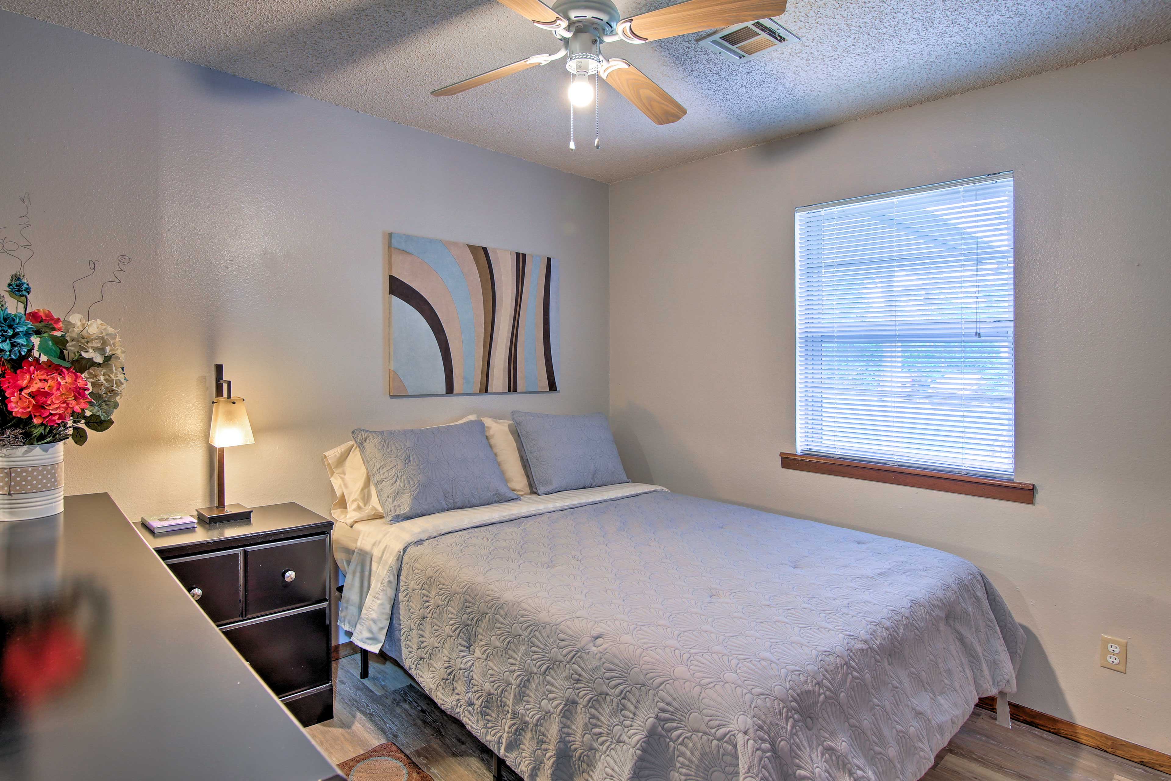 This tranquil bedroom boasts a queen bed and window views.