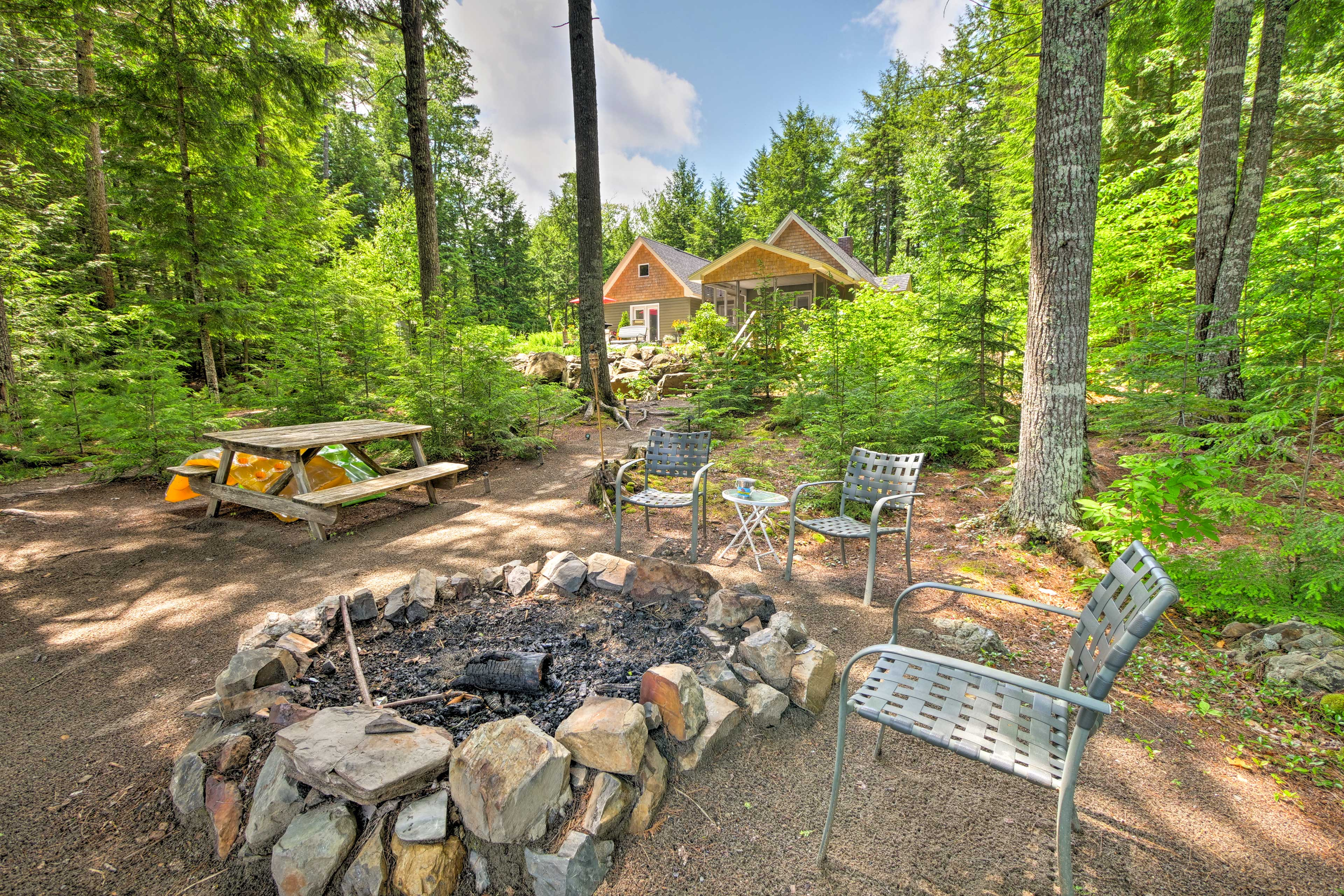Travel towards the water to find a large fire pit and picnic table.