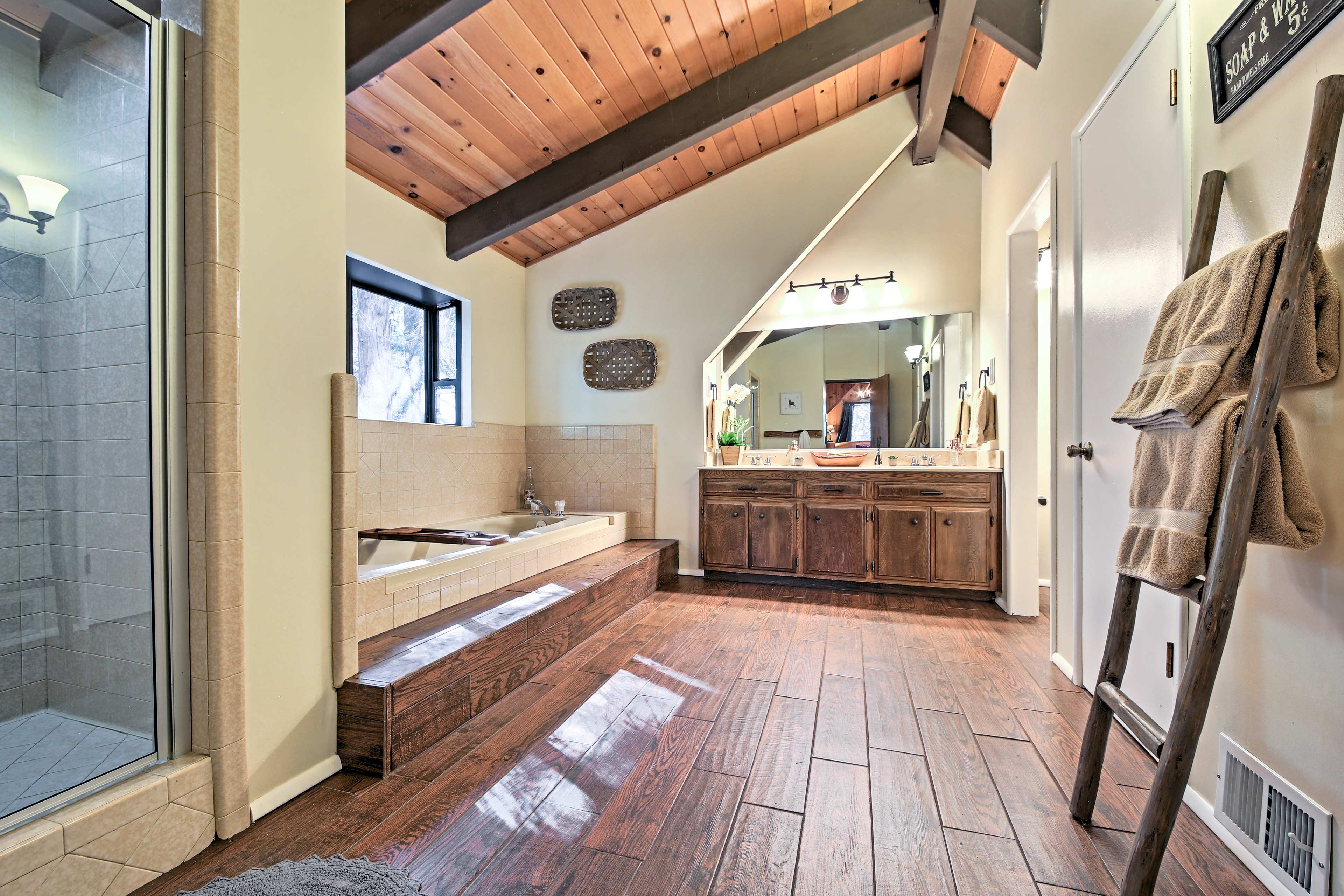 The luxurious master bath hosts a glass-enclosed shower and large sunken tub.