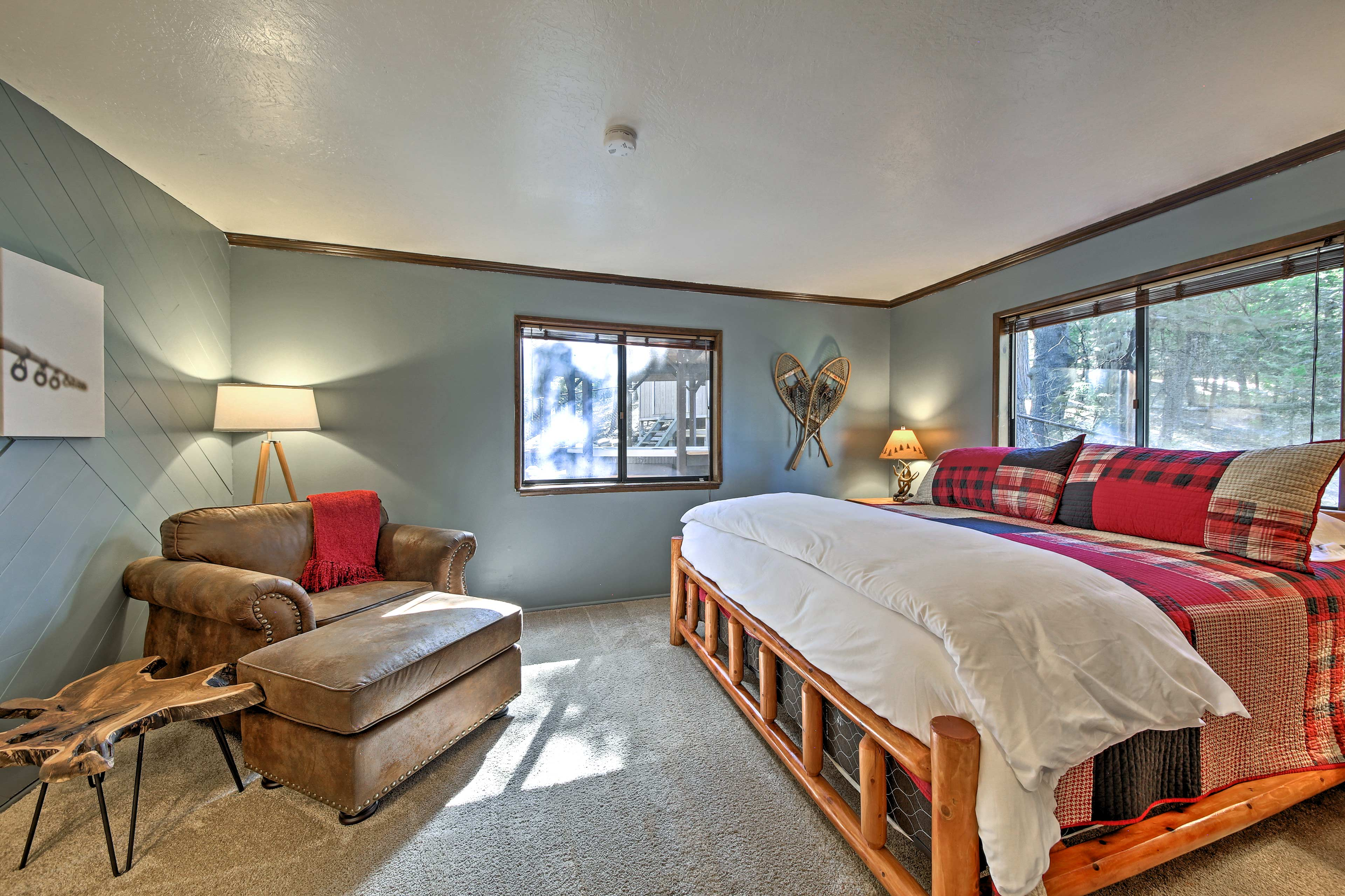 A king bed and plush chair furnish this corner bedroom.