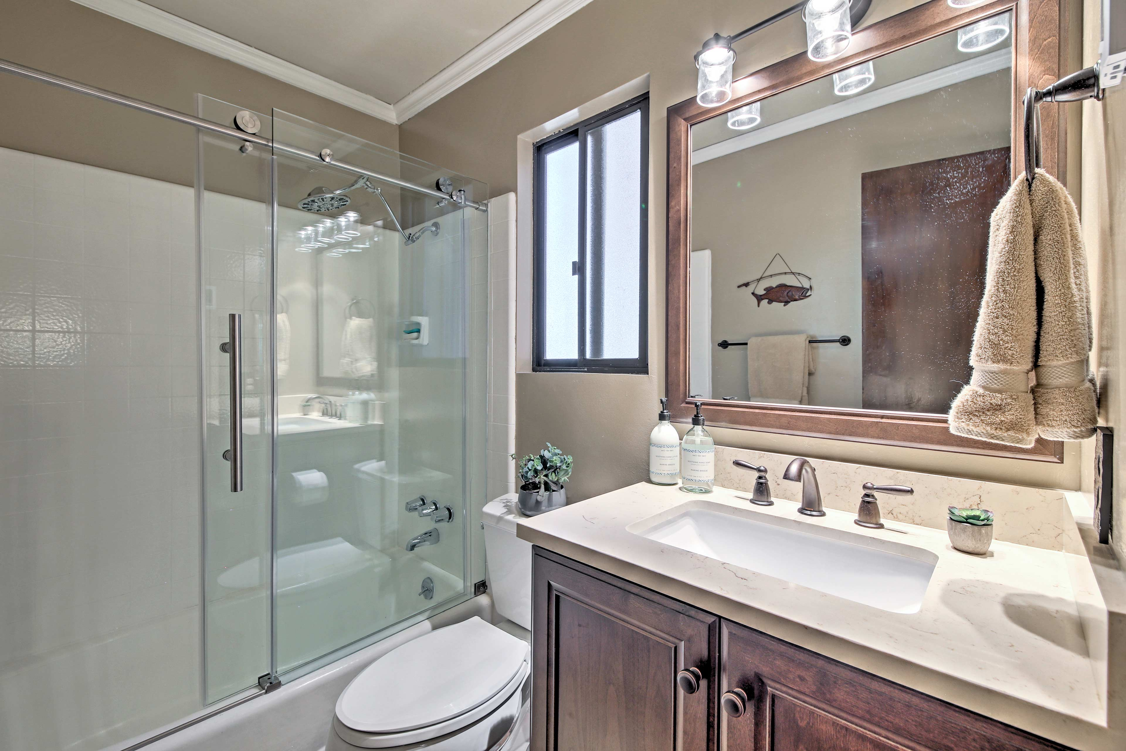 Wash off sand from the beach in the glass-enclosed shower/tub combo.
