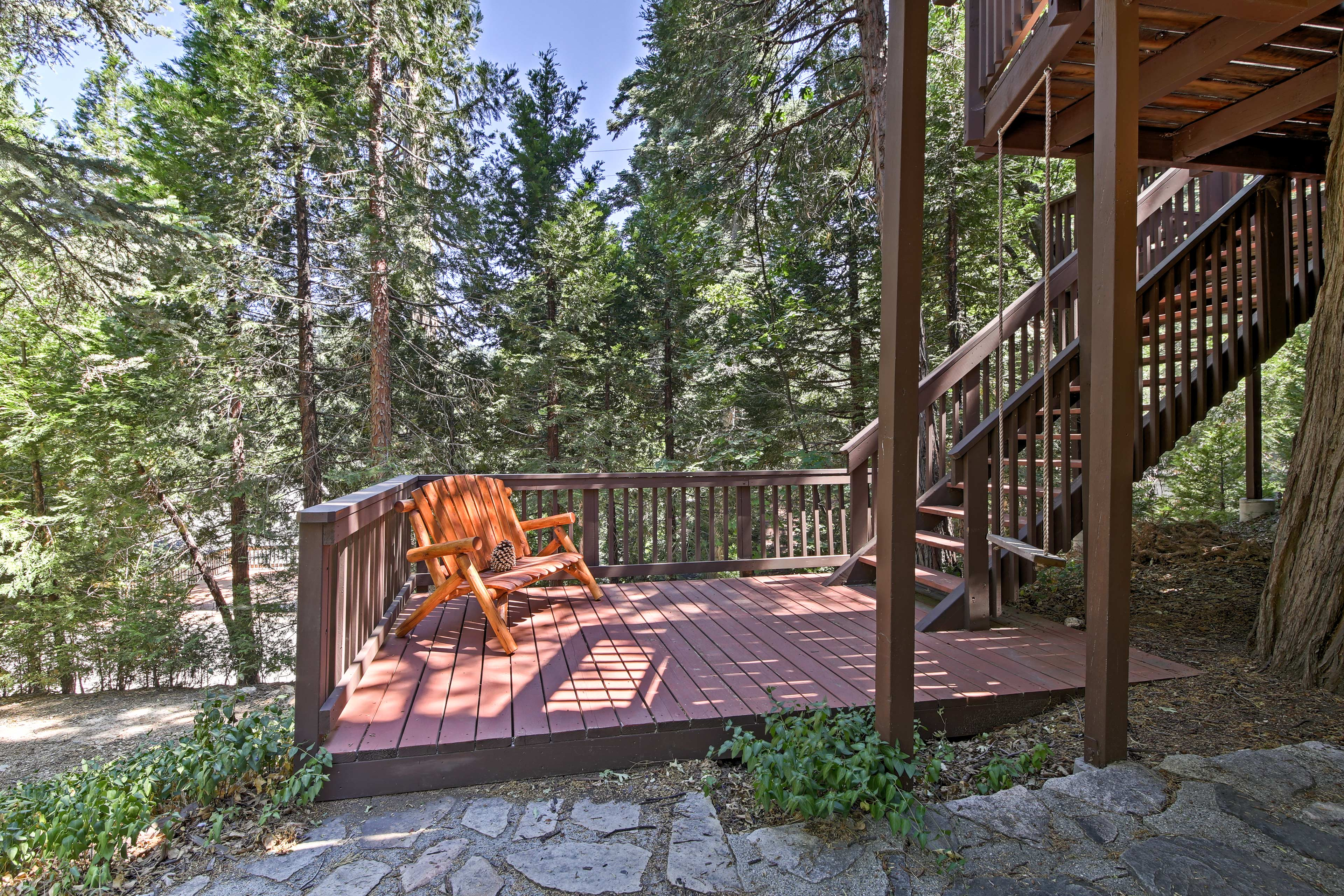 A swing and bench furnish the lower level of the deck.