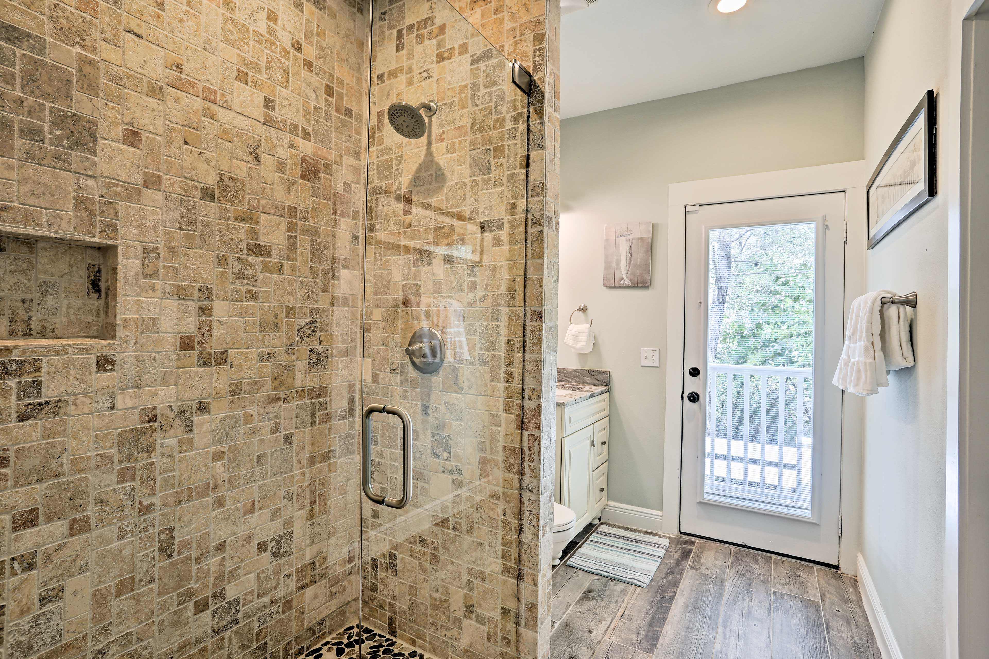 This full en-suite bath boasts a walk-in shower and outdoor access.