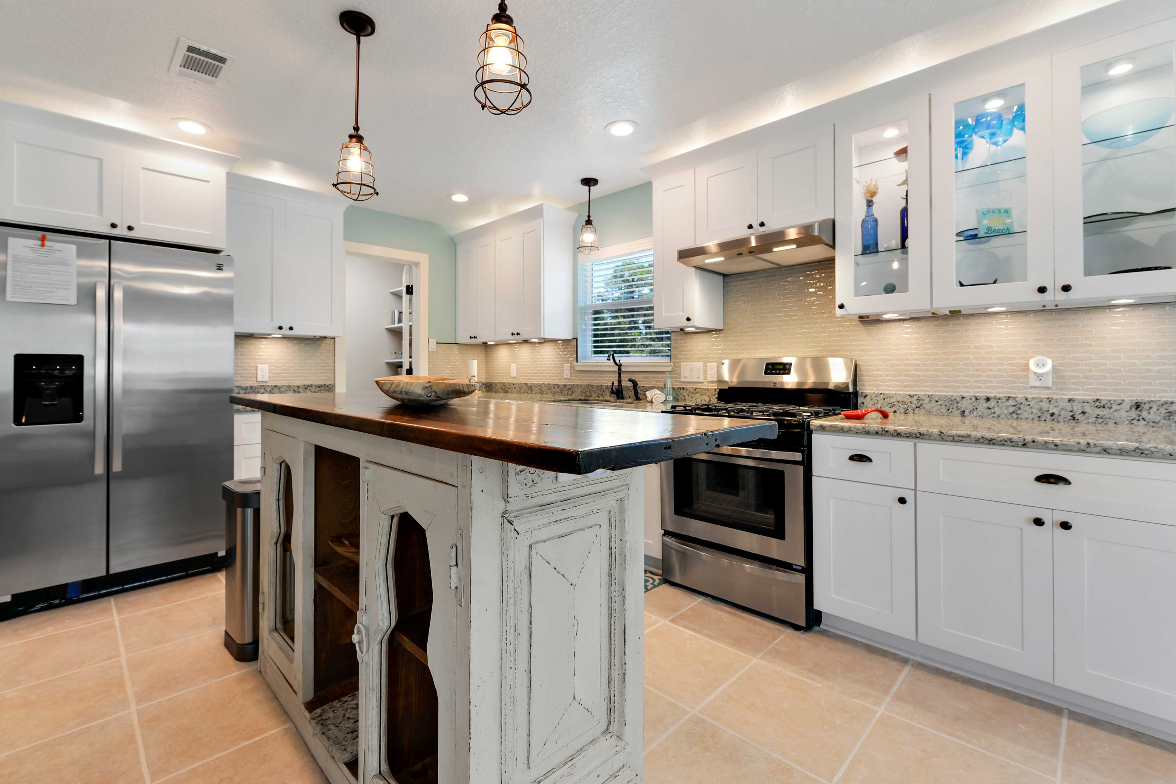 The fully equipped kitchen features an island and stainless steel appliances.