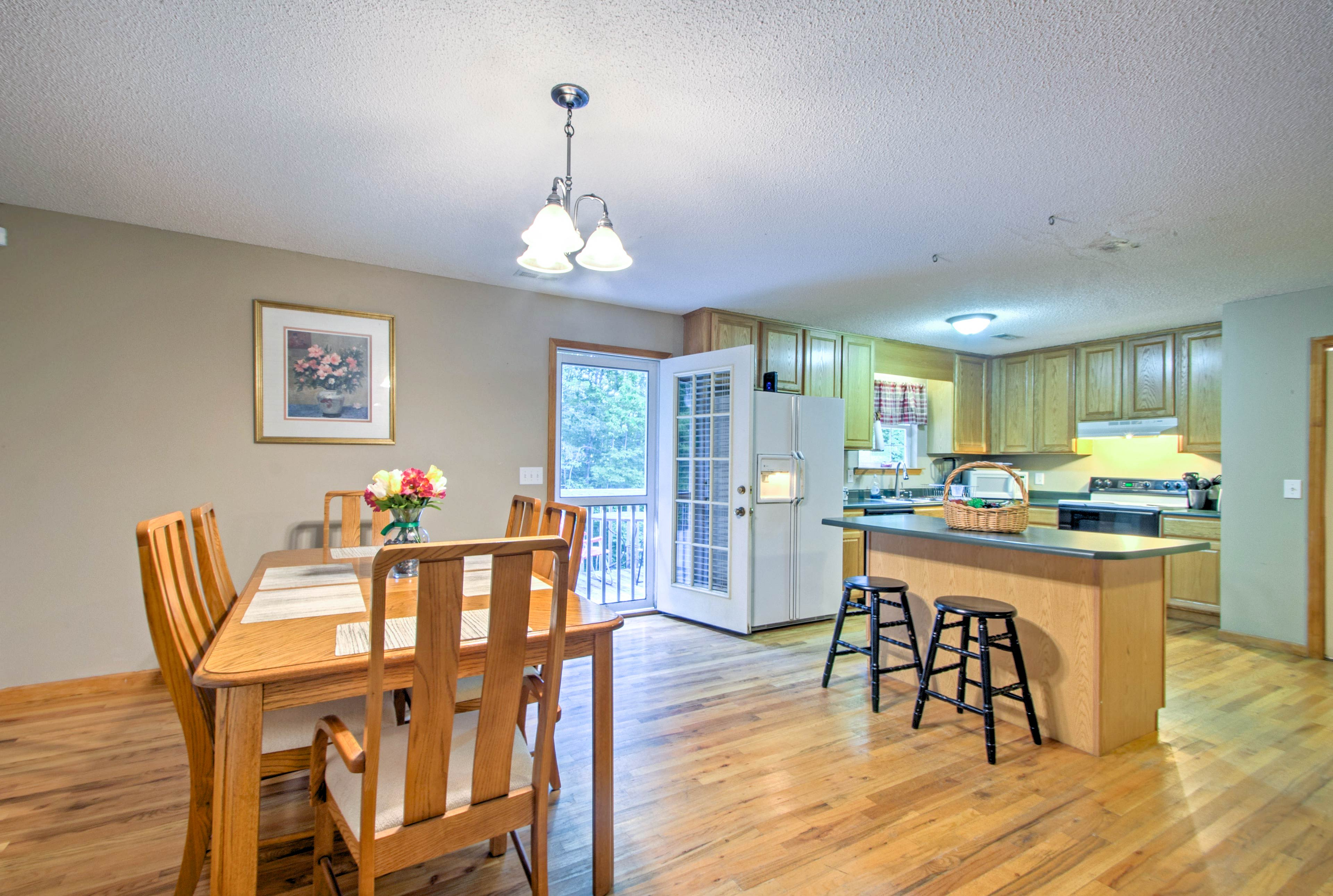 A 6-person wooden table and breakfast bar provide dining options.