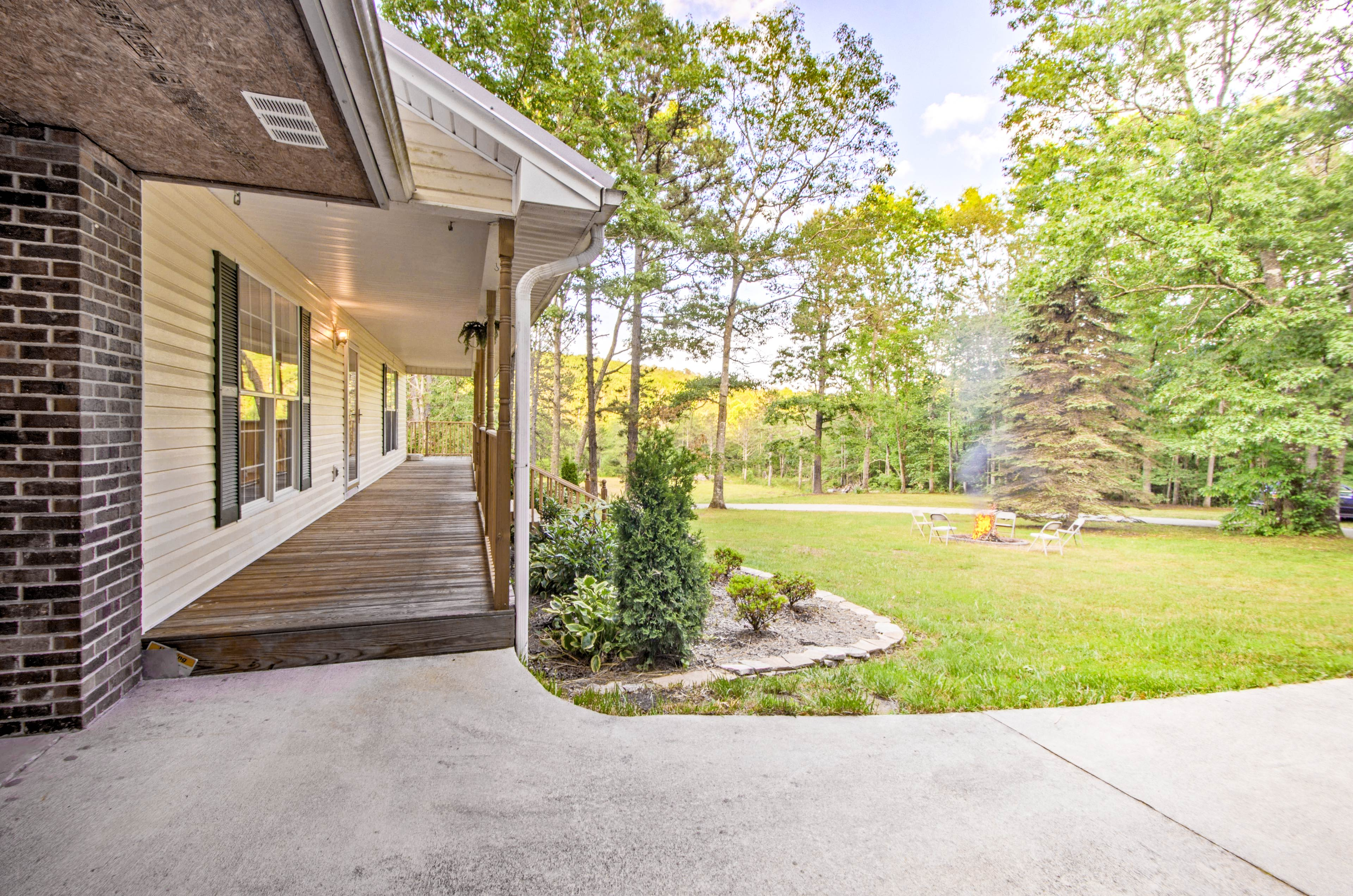 The covered front porch overlooks the fire pit and wooded property.
