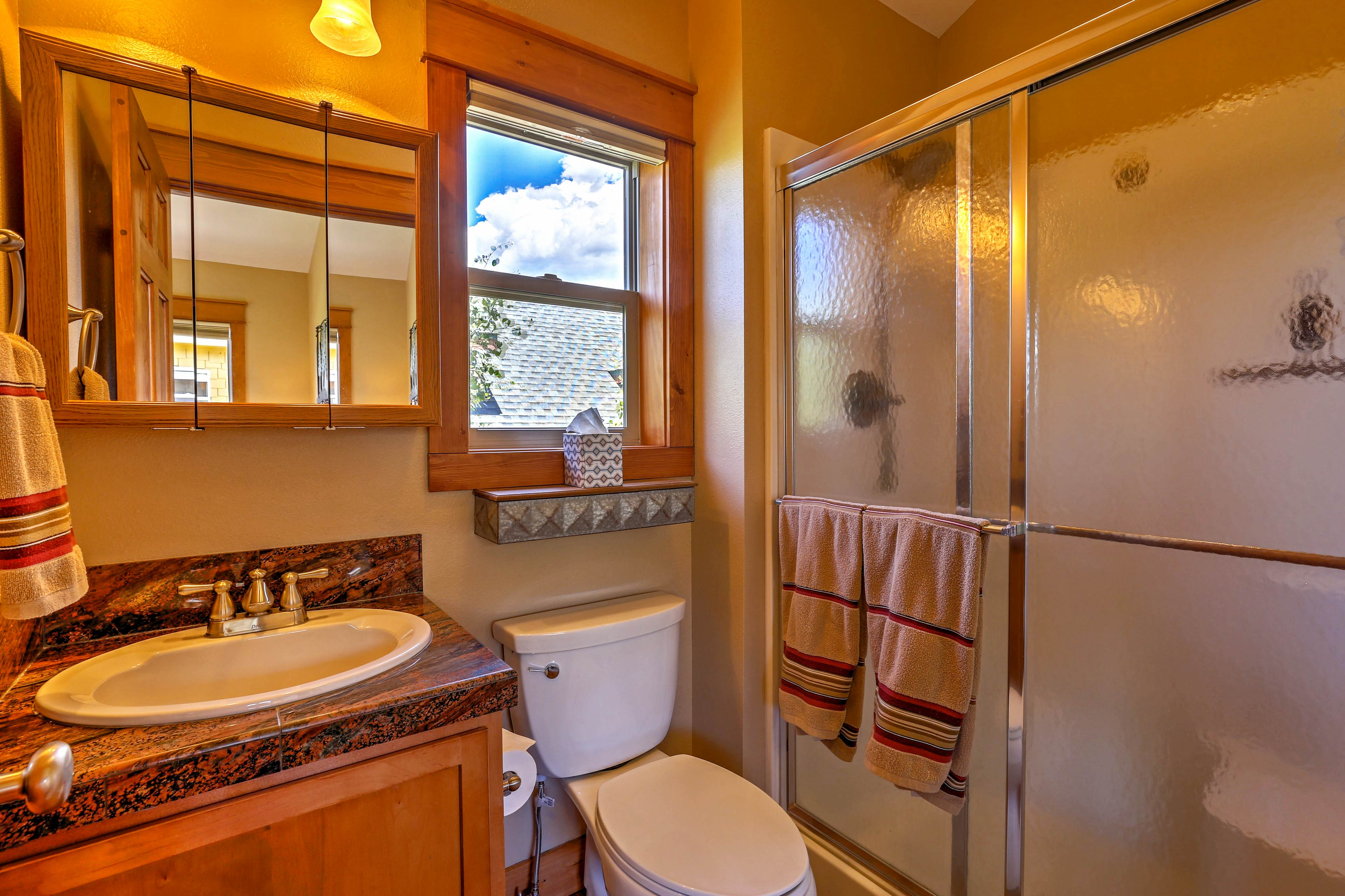 A walk-in shower and tri fold vanity furnish this full bathroom.