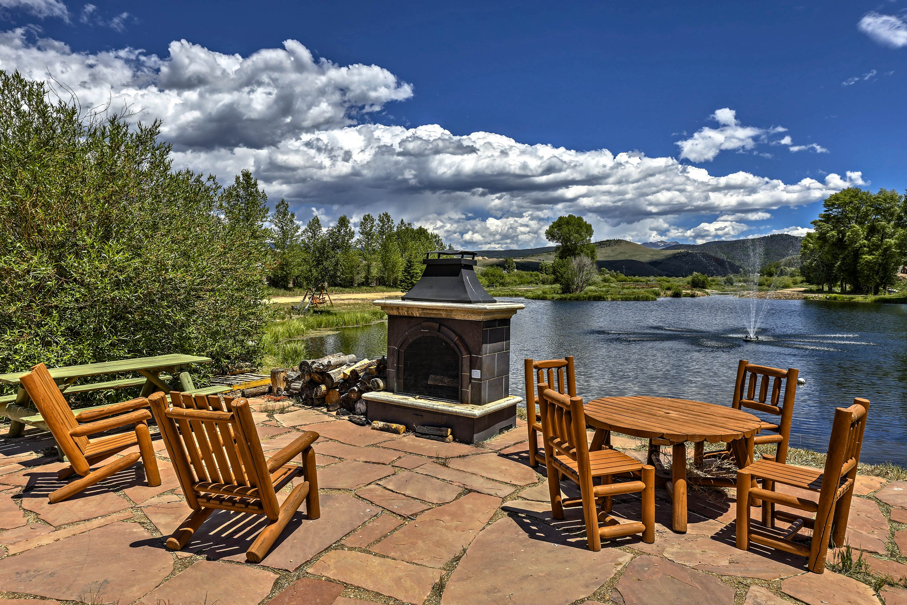 Light up the outdoor fireplace beside the pond and sip your favorite drink.