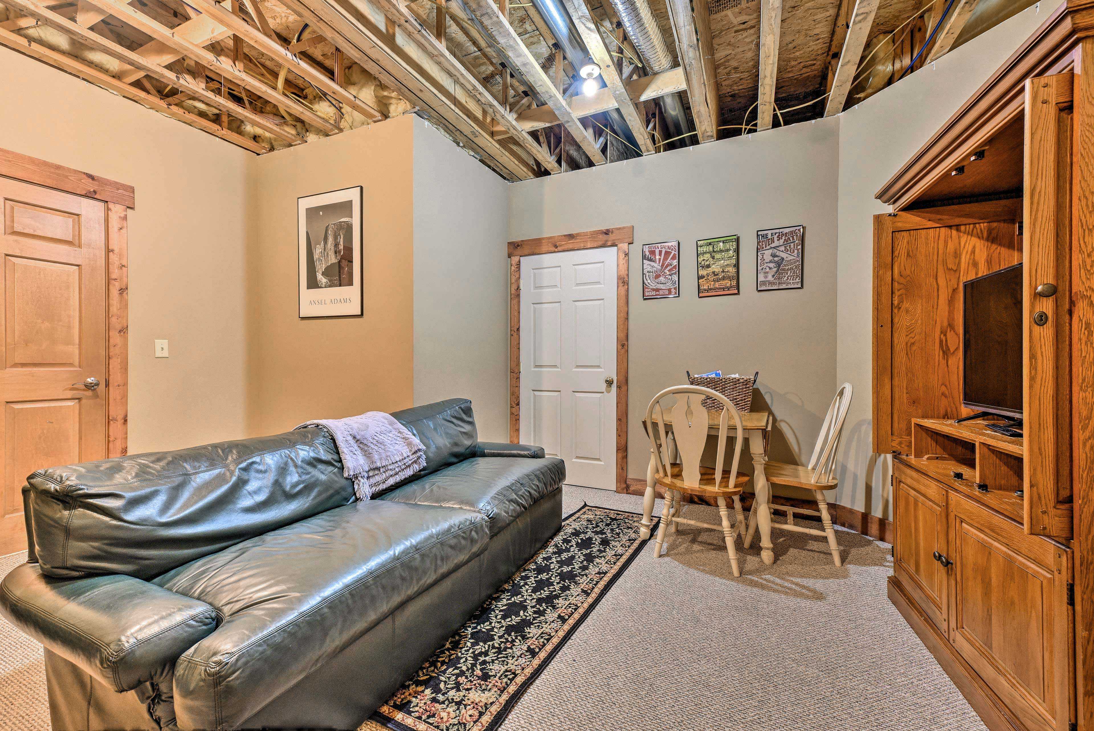 The basement is complete with a comfy couch, TV, and third bedroom.
