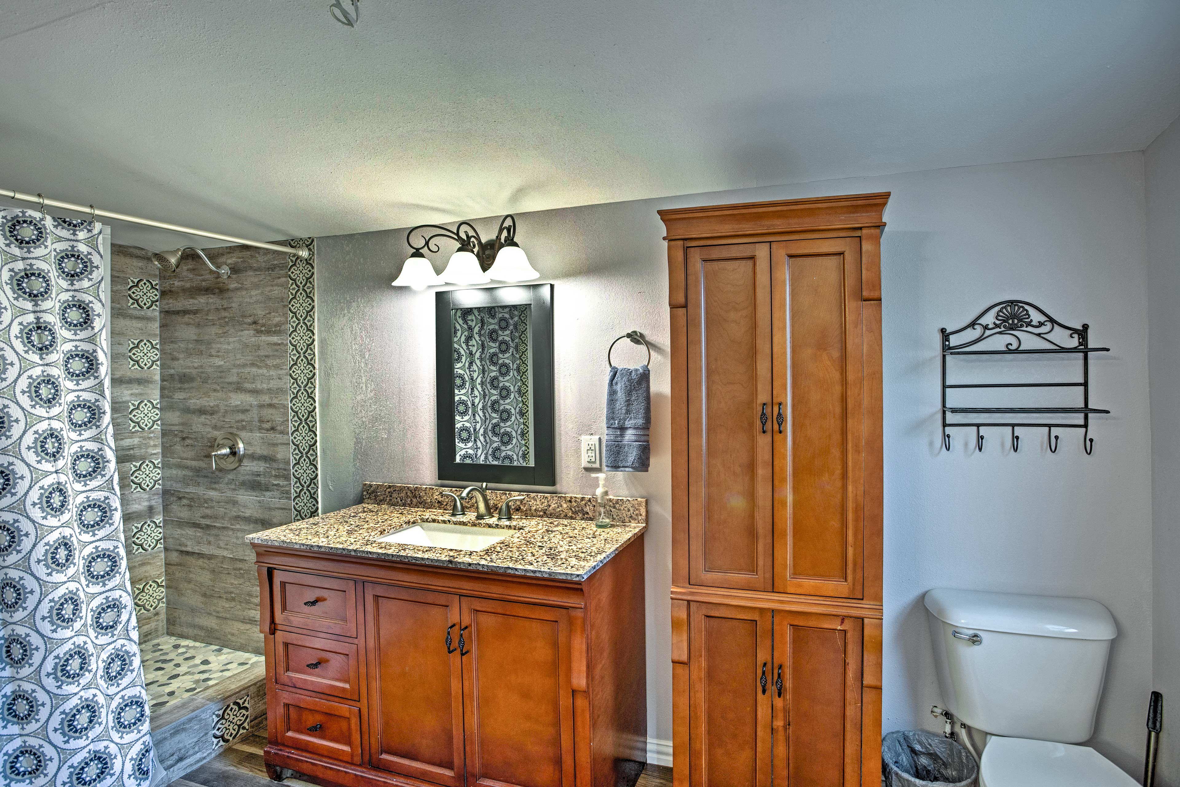 The bungalow has a full-sized bathroom with an elegant stone walk-in shower.