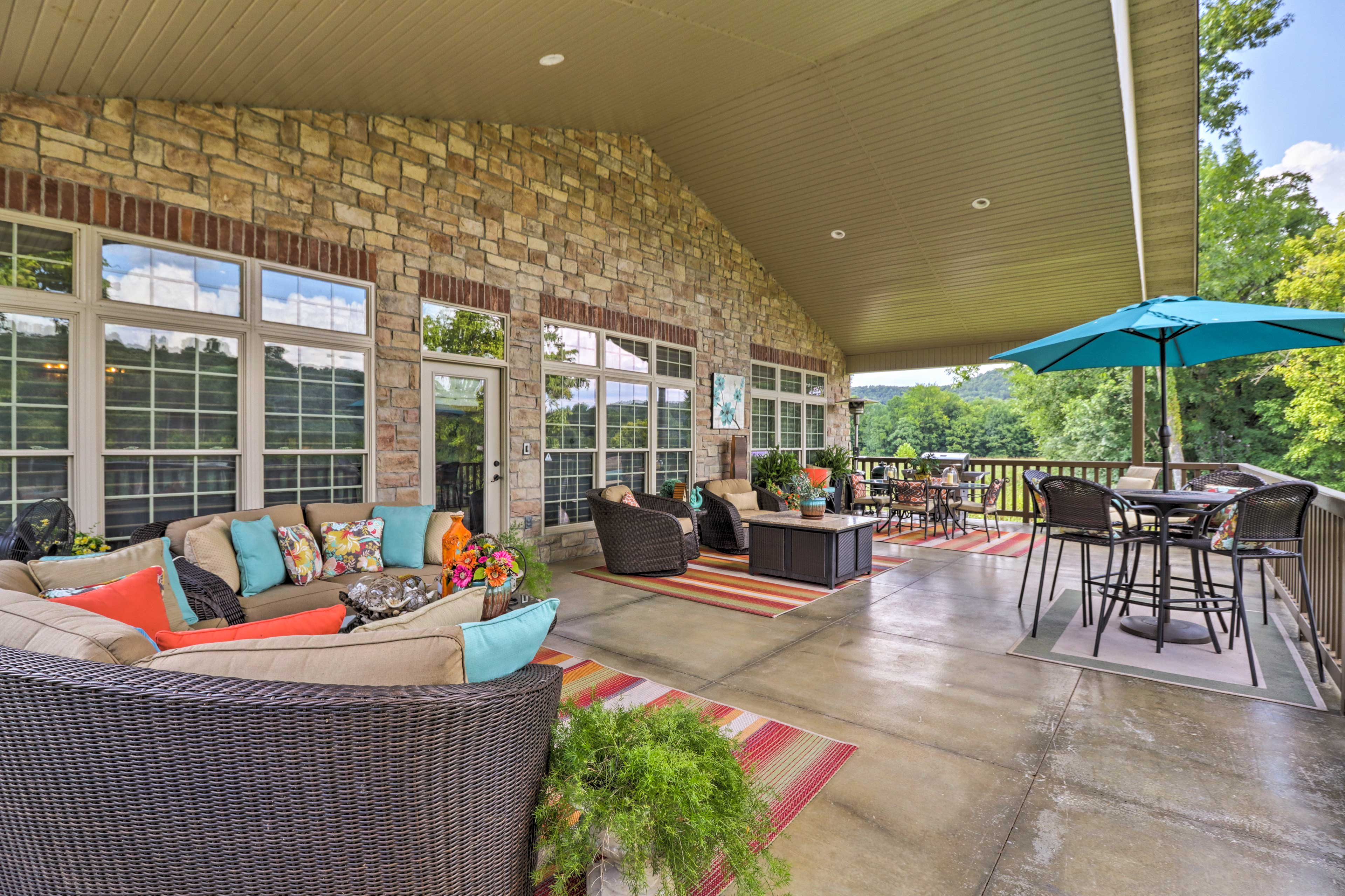 The expansive covered deck has a gas grill, gas heating lamp, and umbrella.