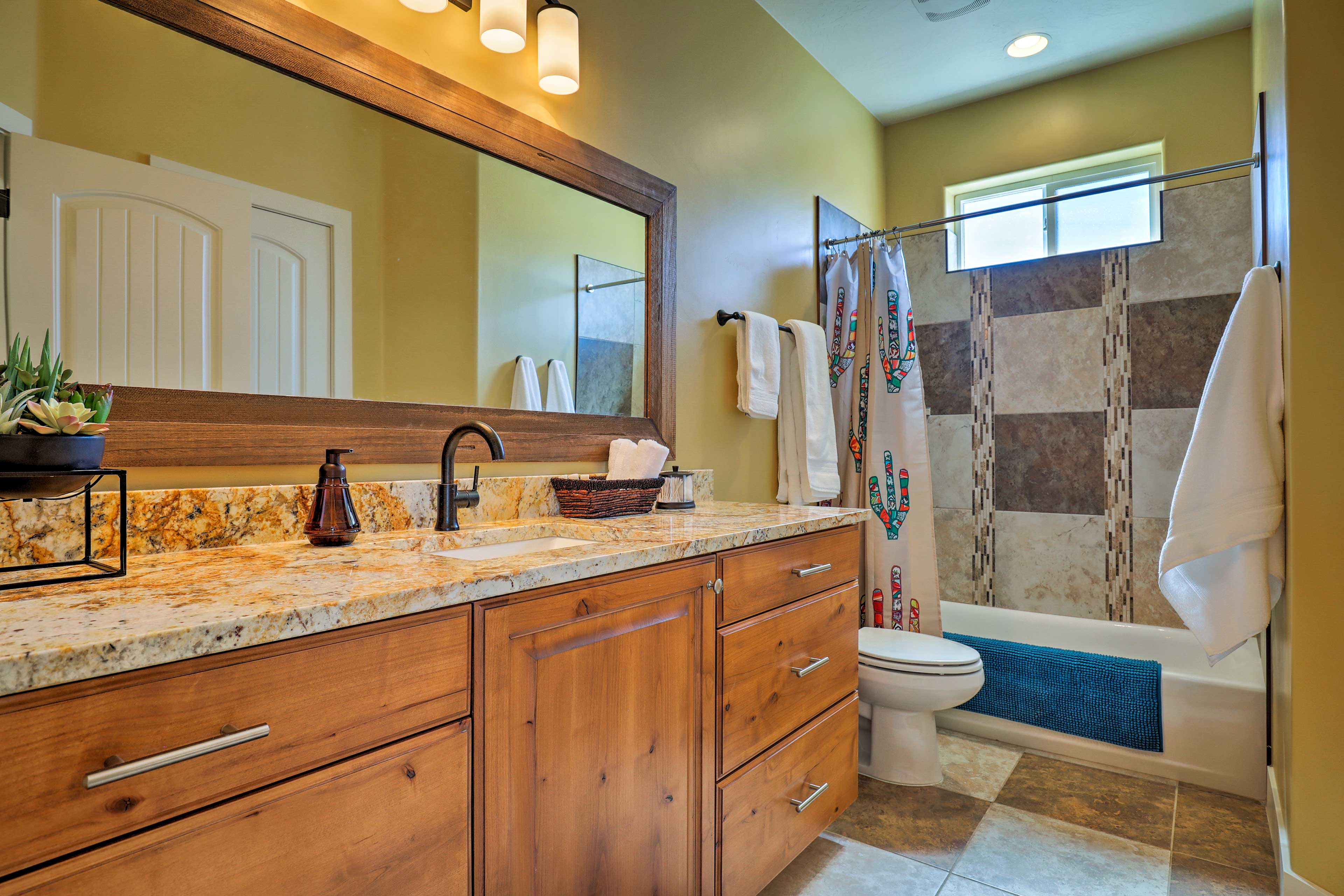 This bathroom has a shower/tub combo and a large vanity.