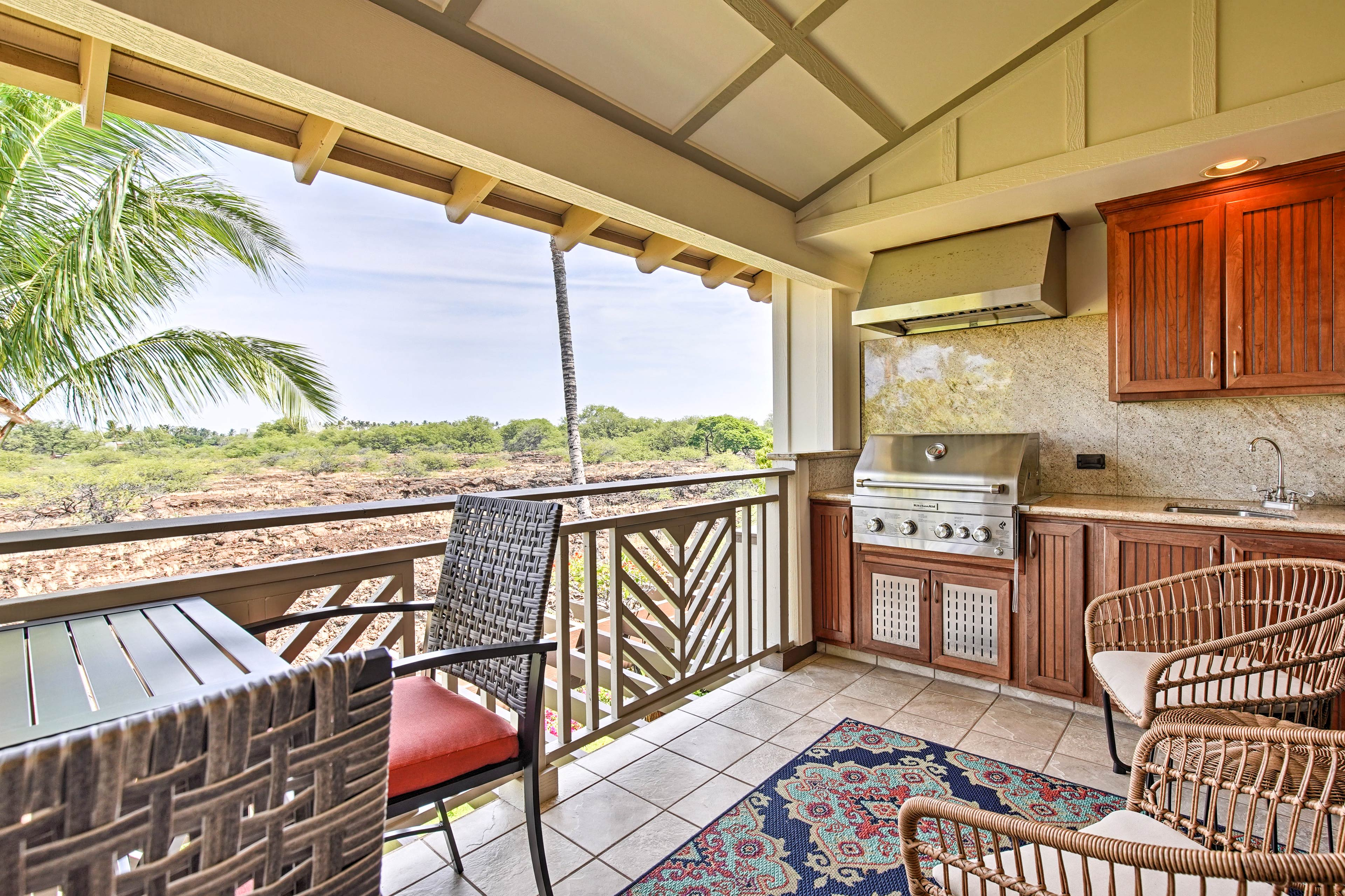 The covered lanai is the ideal spot with a gas grill, comfy furniture, and views
