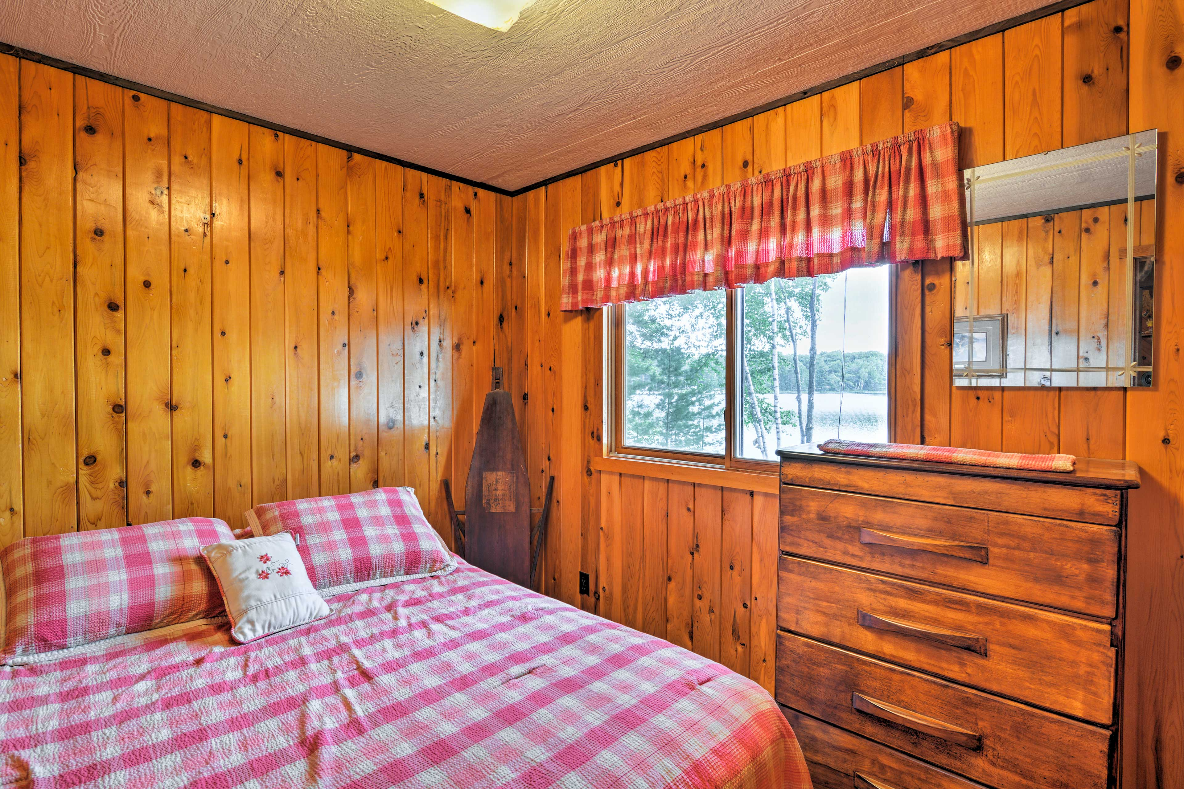 The master bedroom boasts a queen bed and views of Gooseneck Lake.