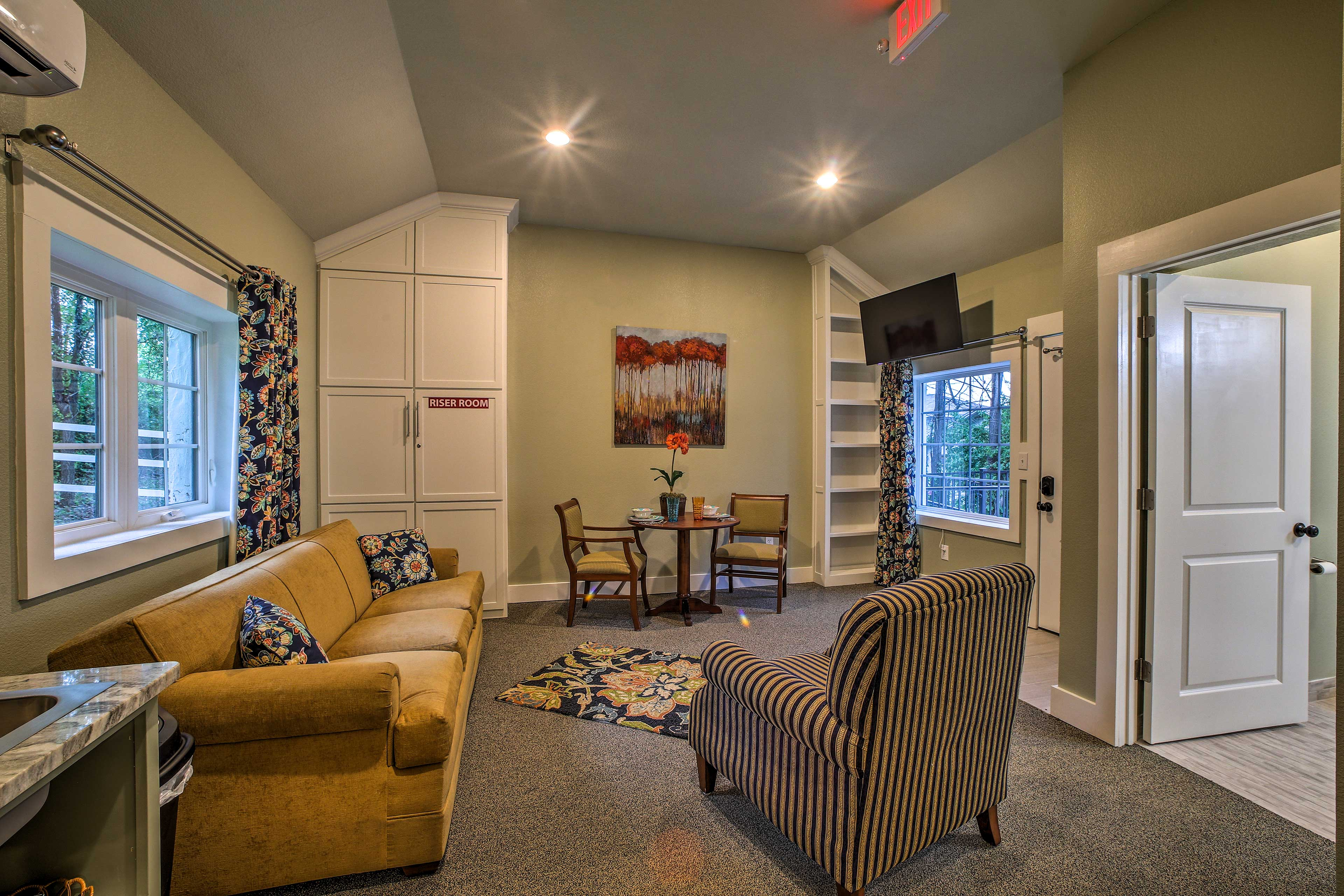 The living room has tall ceilings and a flat-screen cable TV.